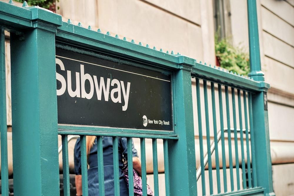 Subway signage on cyan metal fence