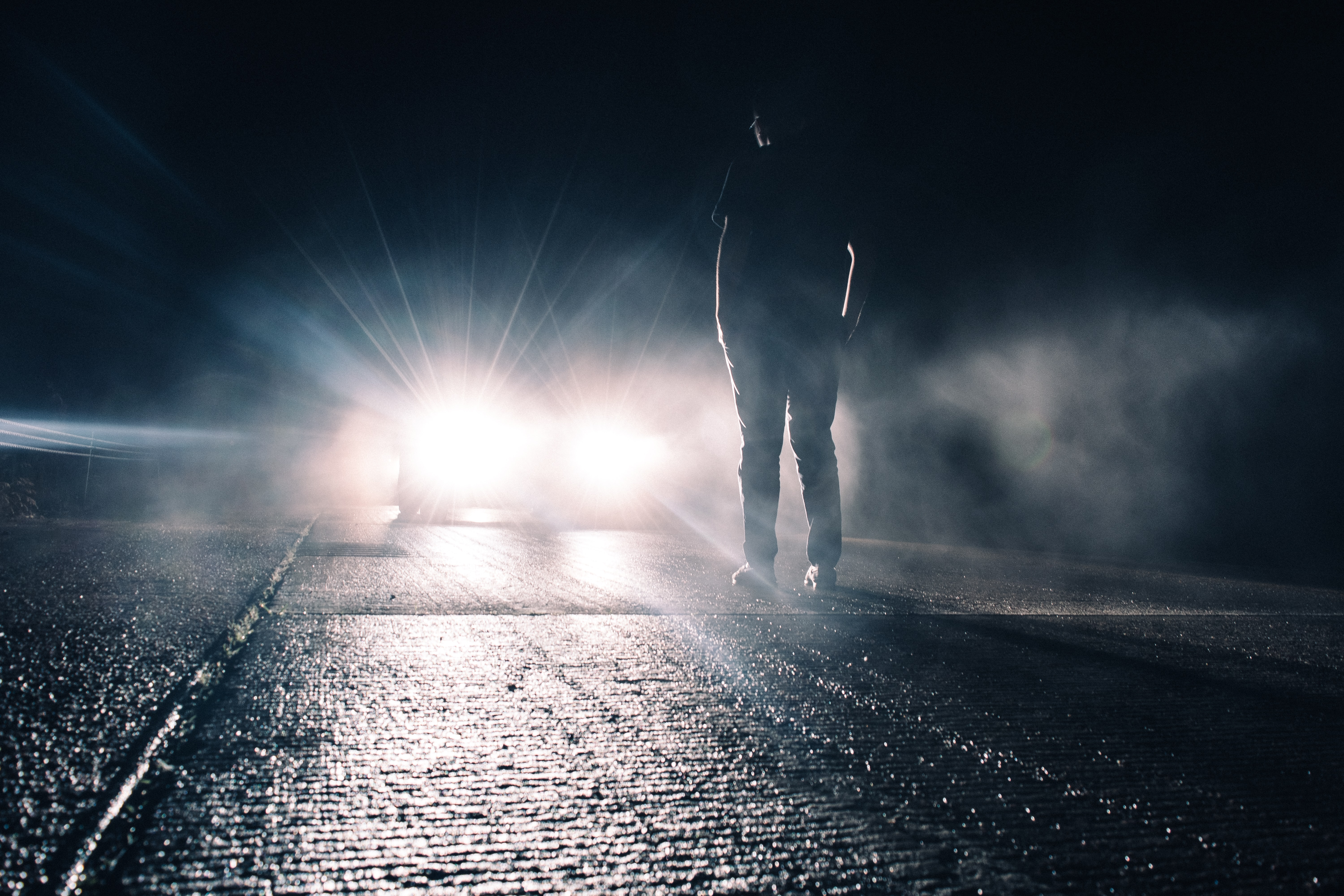A man standing in the dark on the street in front of a headlight shining light at him in Brandon