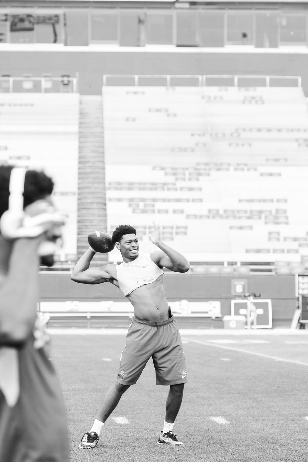 grayscale photo of man playing football