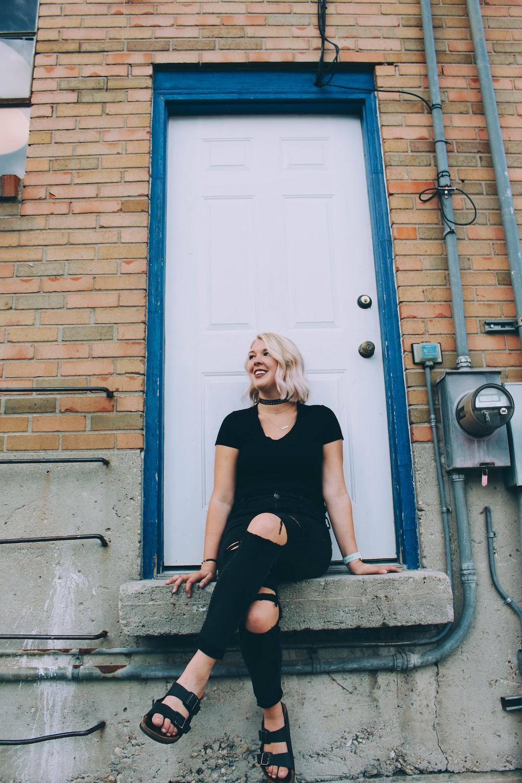 woman in black shirt sitting on concrete floor