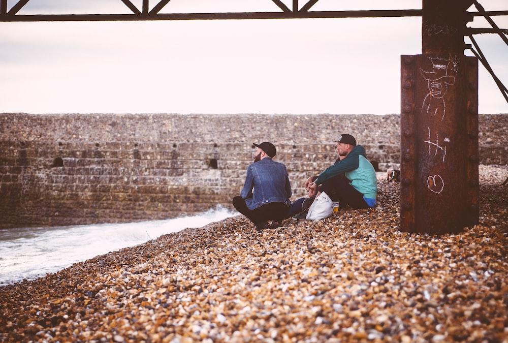 two men sitting near body of water