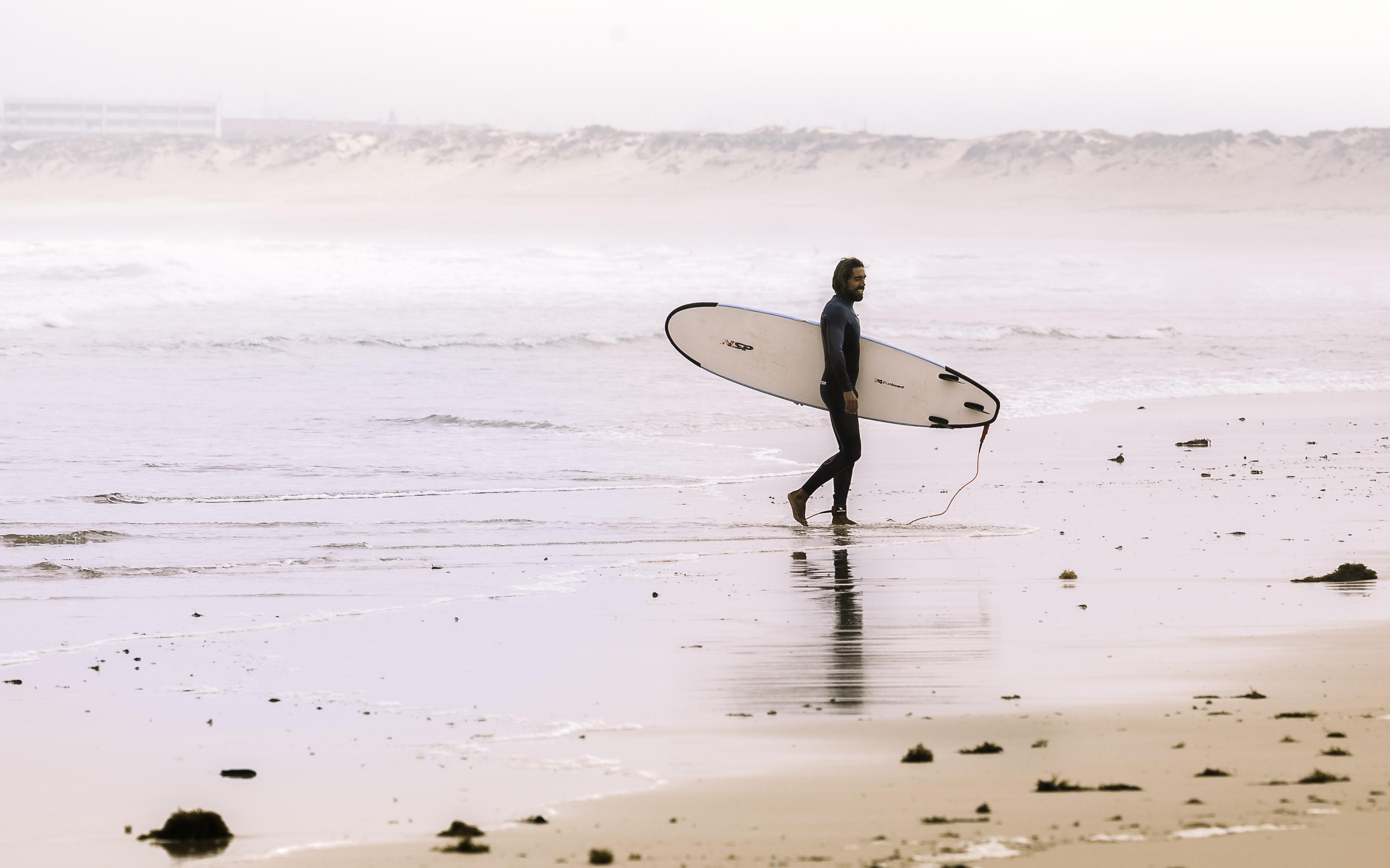 A male wearing a wetsuit holding a surfboard walking by the ocean in Praia de Peniche de Cima