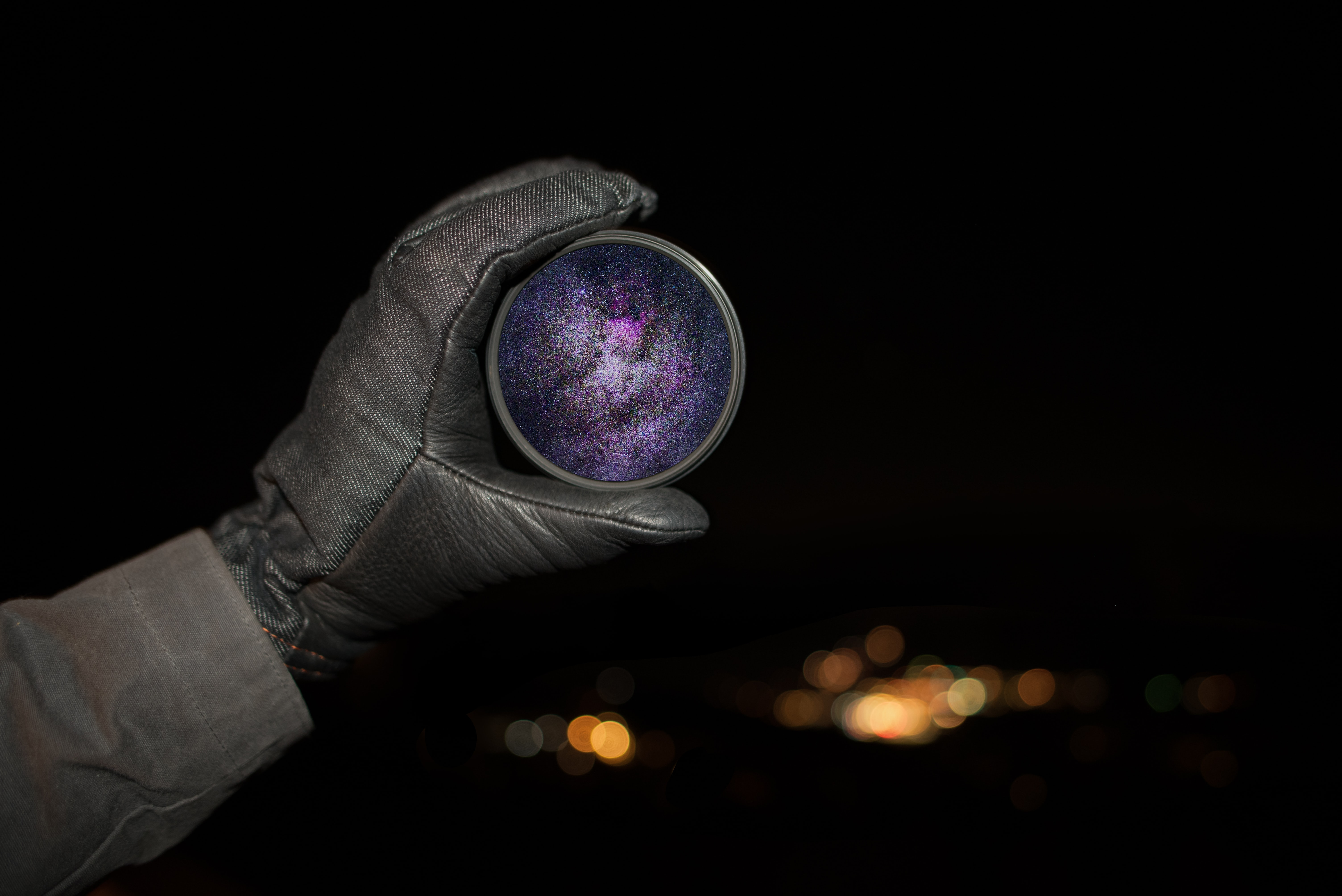 A person holding a lens filter with the galaxy and stars on it in Silverthorne