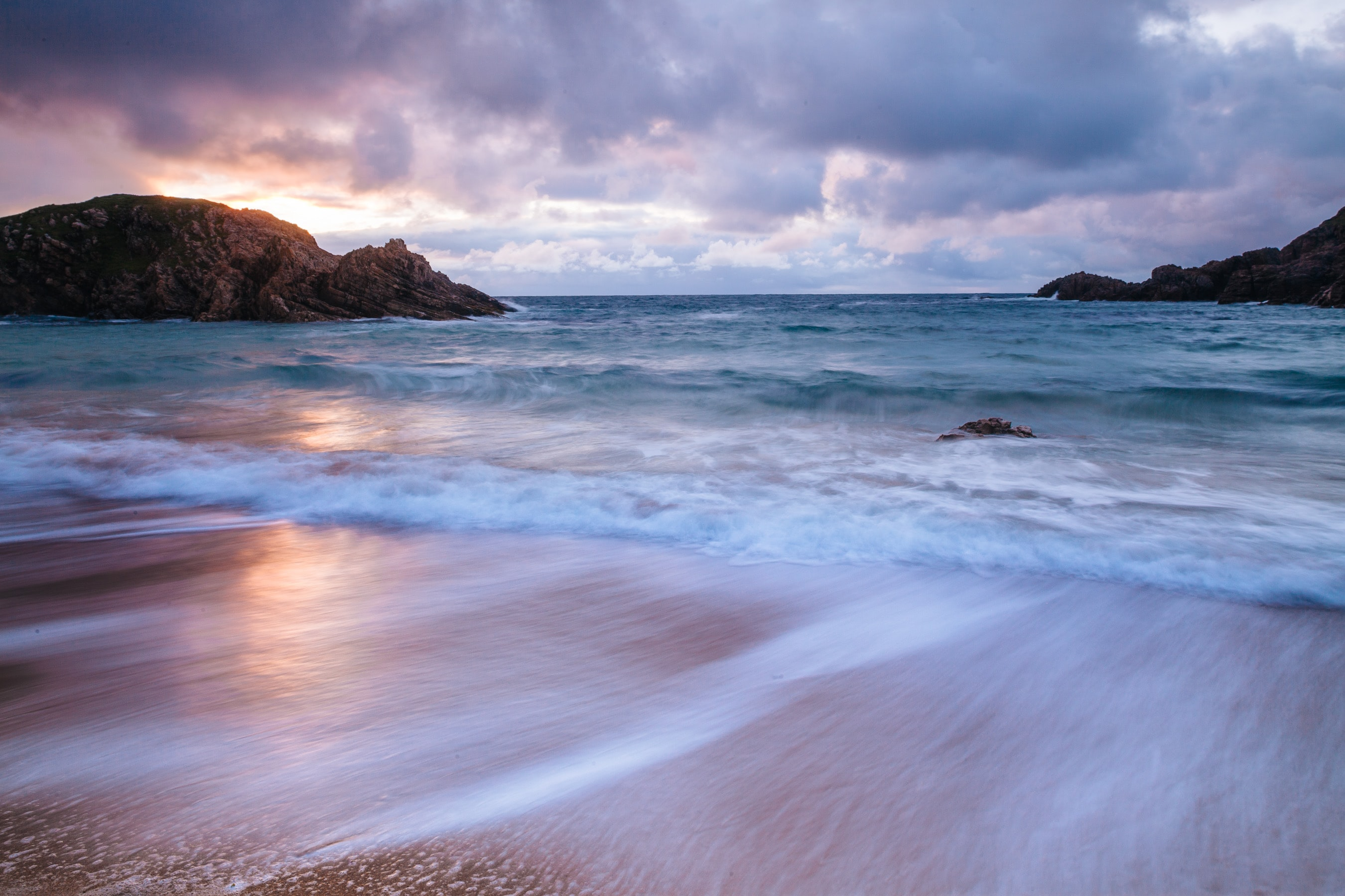 Ocean waves recede on a cloudy day in County Donegal, Ireland during sunset