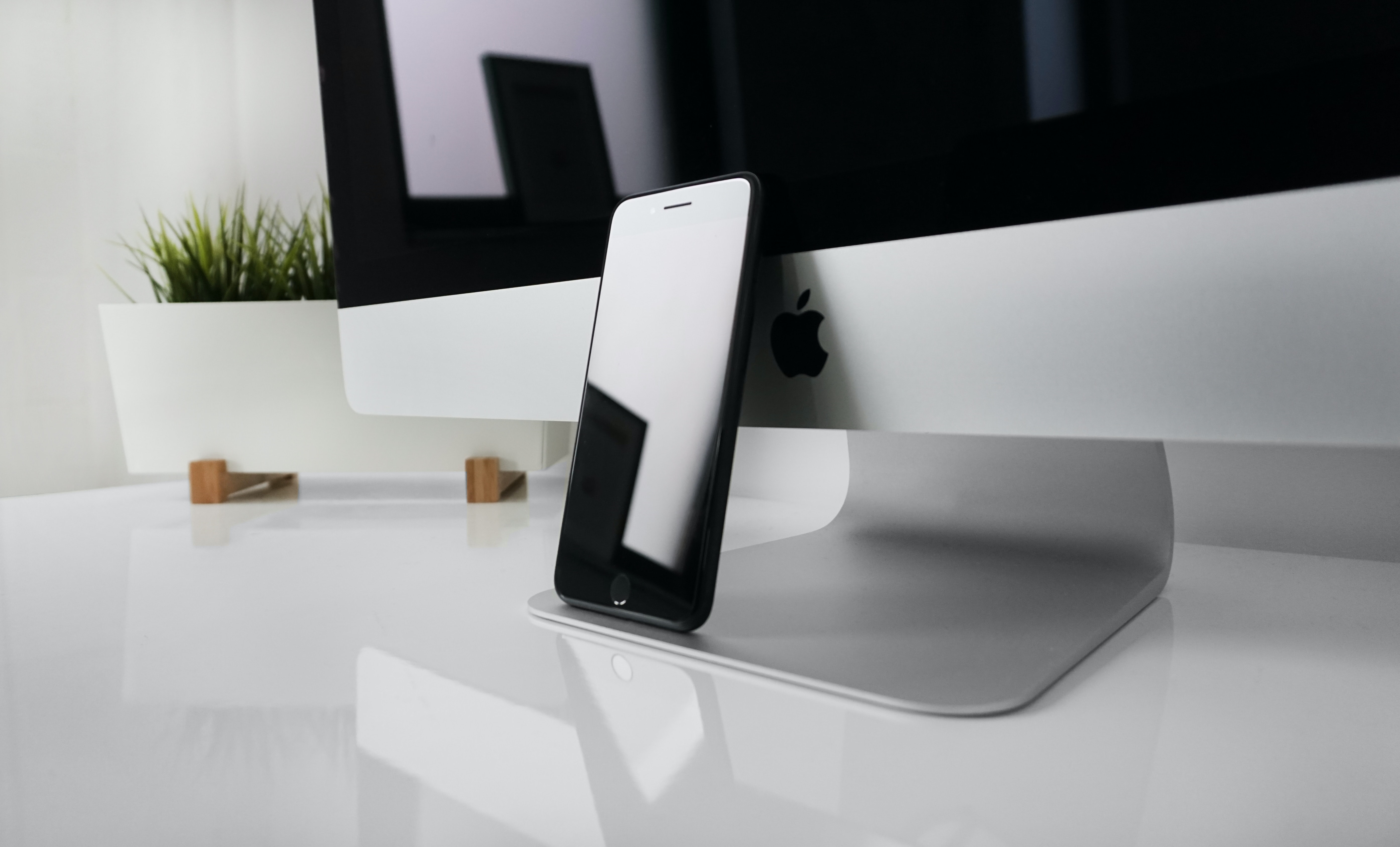 An iPhone leaning against an iMac on a white glossy desk
