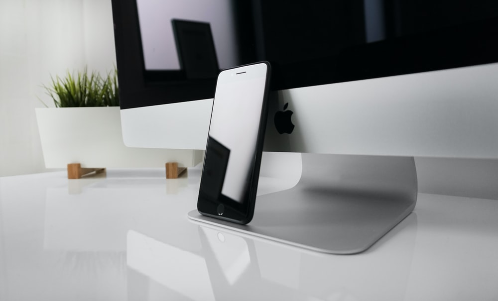 black iPhone 7 leaning on silver iMac