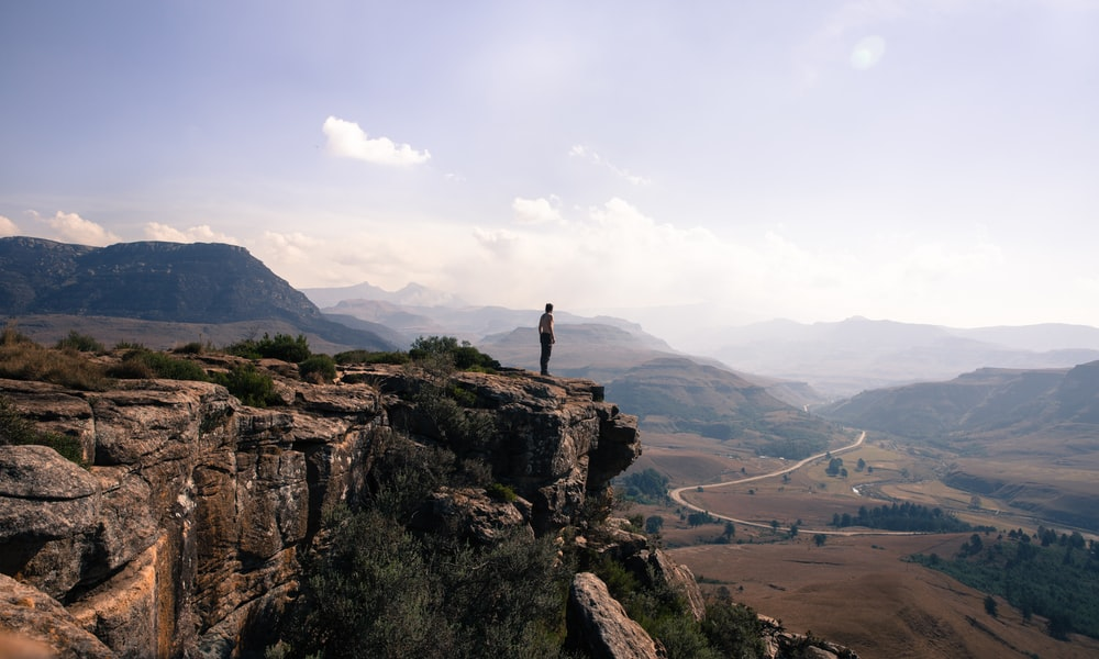 A man standing on the edge of a cliff overlooking a winding road in Sani Pass