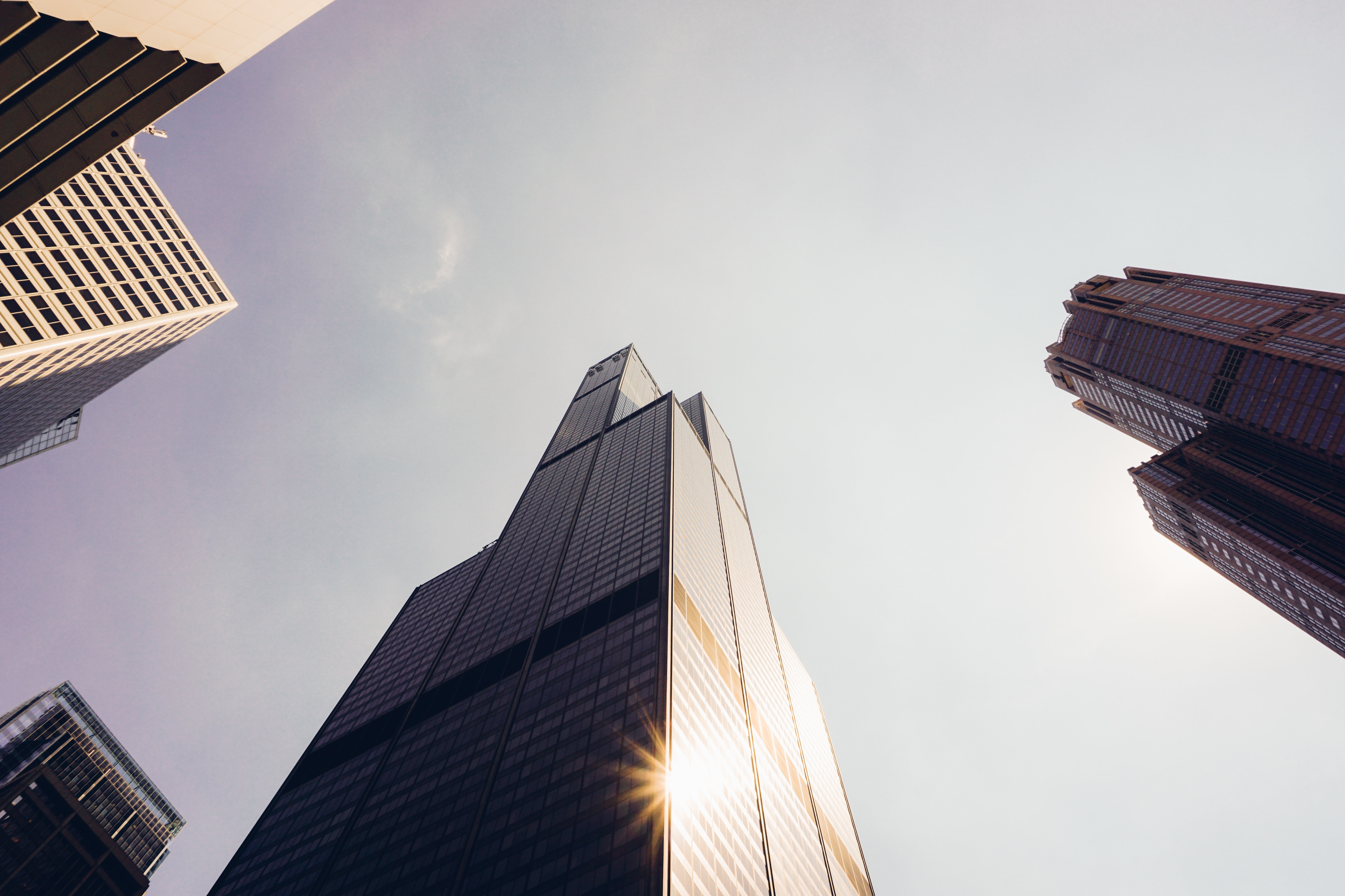 A low-angle shot of shining sun reflected in the windows of skyscrapers in Chicago