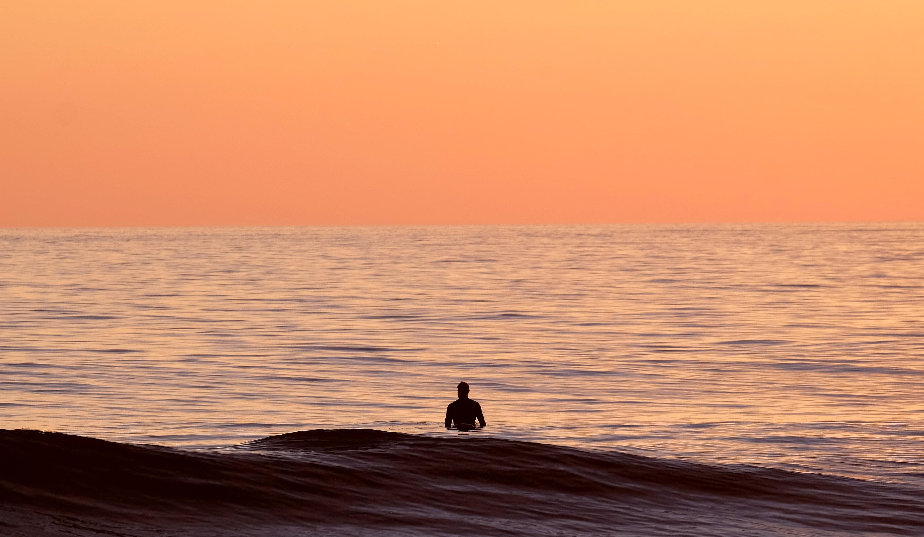 Silhouette of a man waist-deep in the ocean under an orange sky