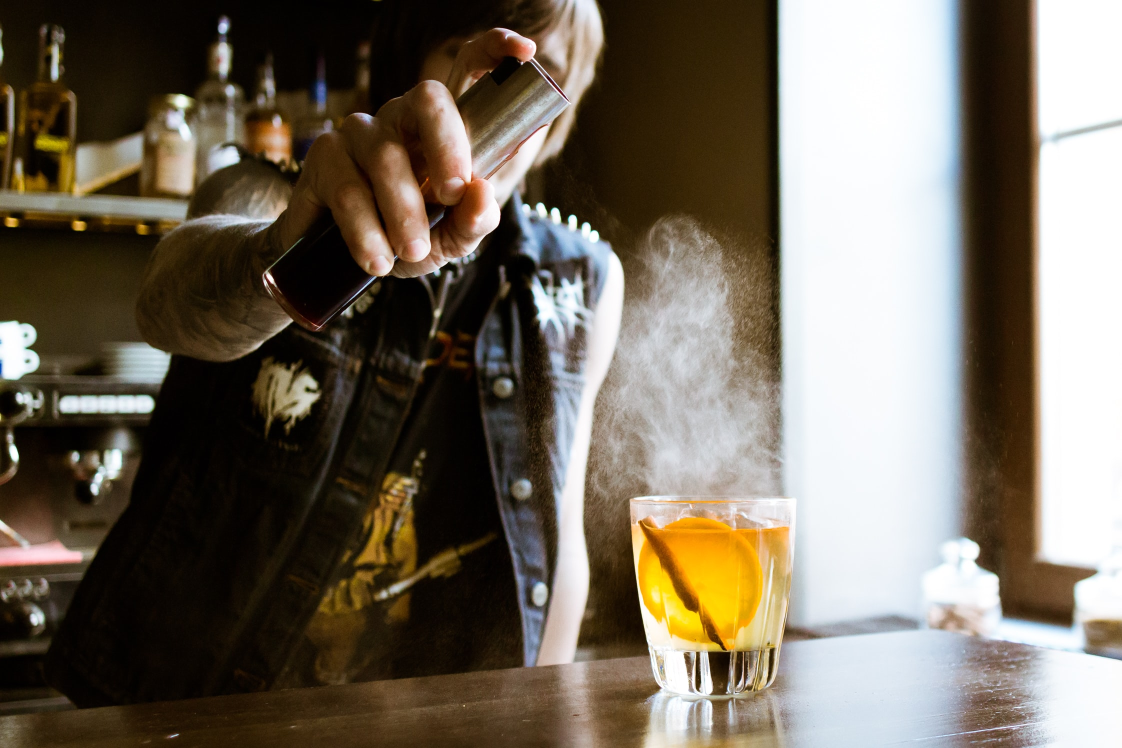 A bartender spraying an a whiskey drink with cocktail in a bar in Vozdvyzhensky