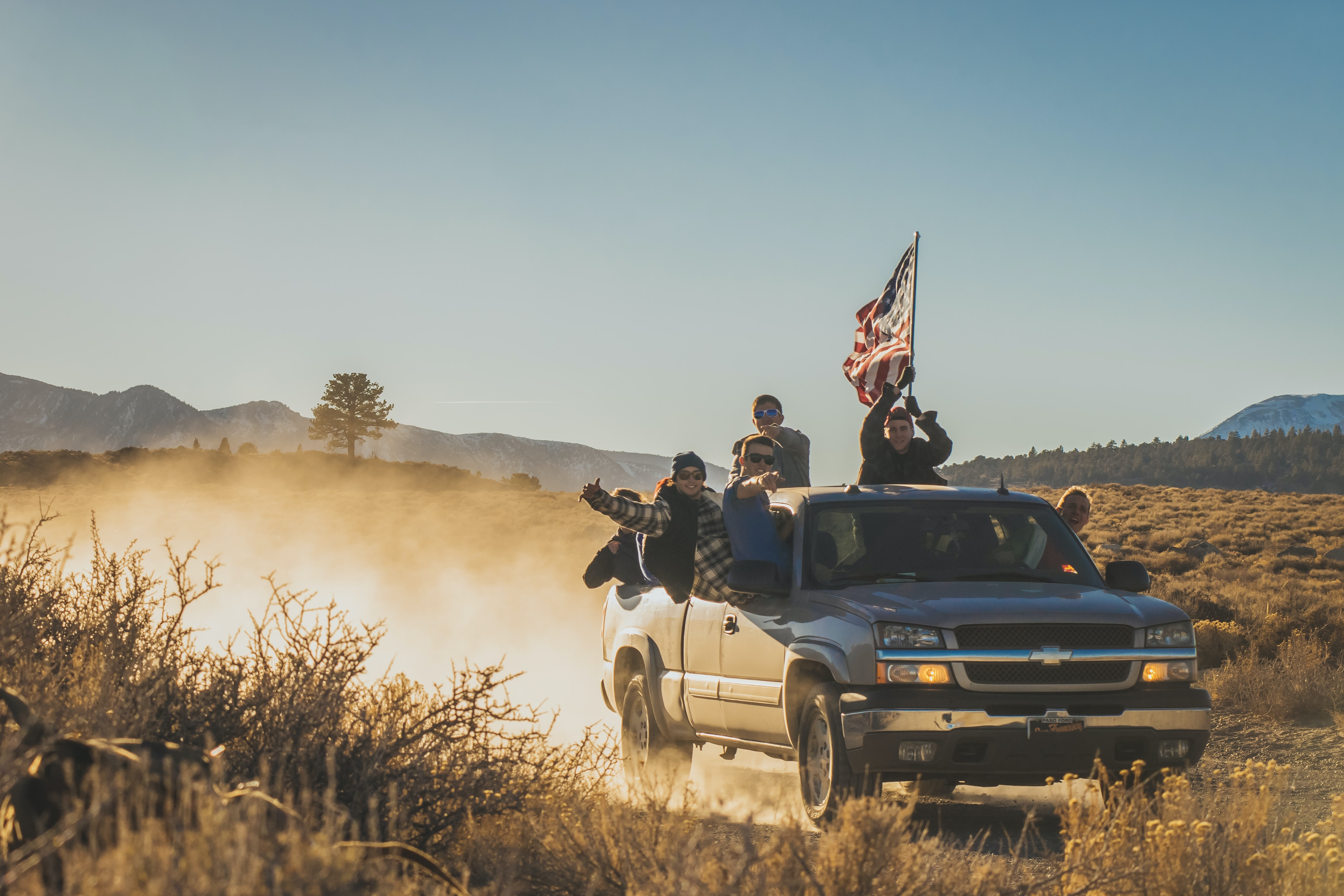Group of guys riding in a Chevrolet through a dirt road in Mammoth Lakes, holding up an American flag
