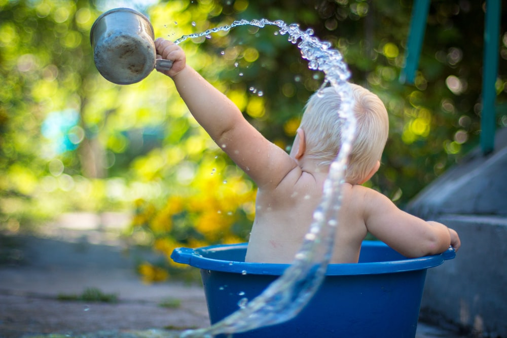 child lifting water dipper