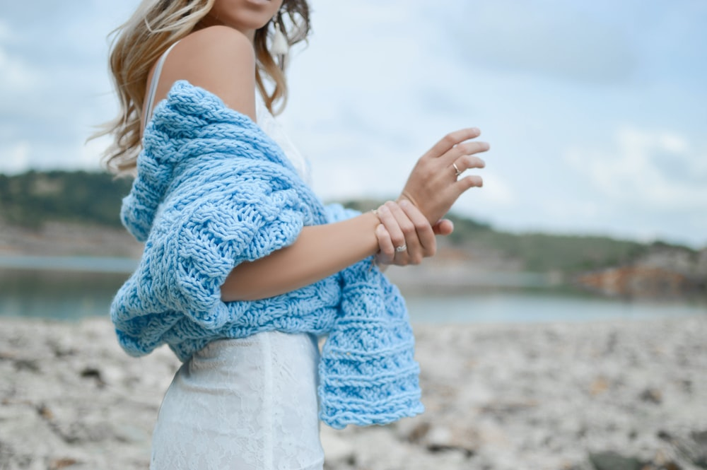woman wearing teal crochet top and white skirt