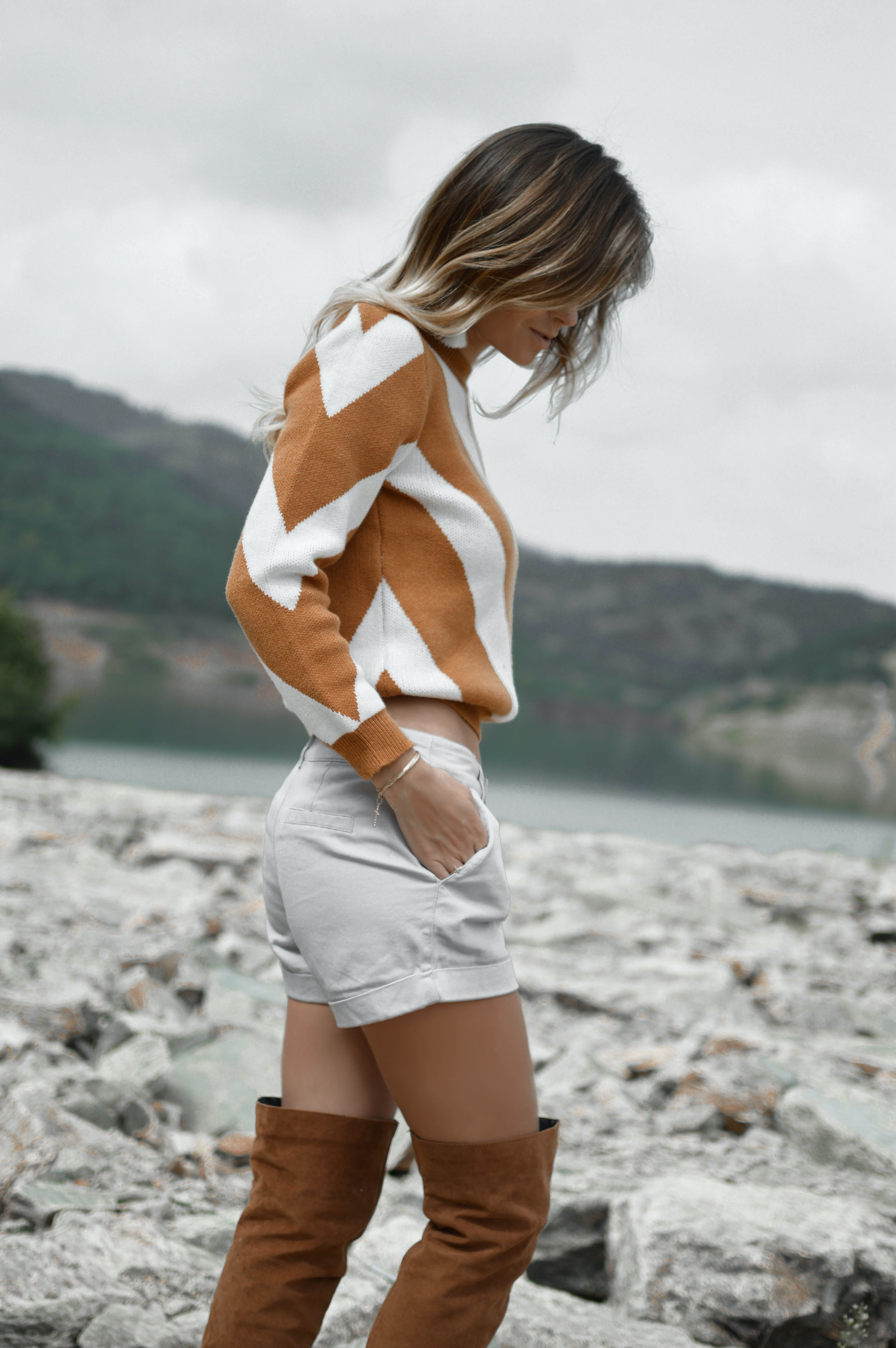 Woman in a chevron sweater and thigh high boots walking over rocks