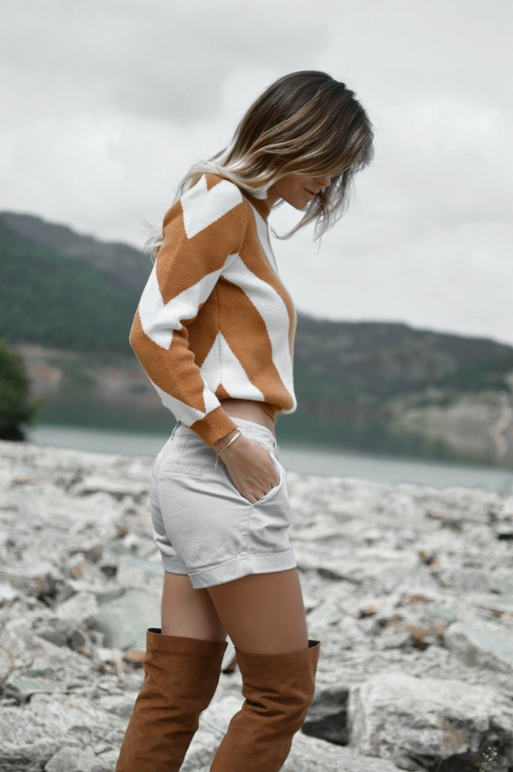 woman in white short shorts looking on rocks while putting her hand in pocket