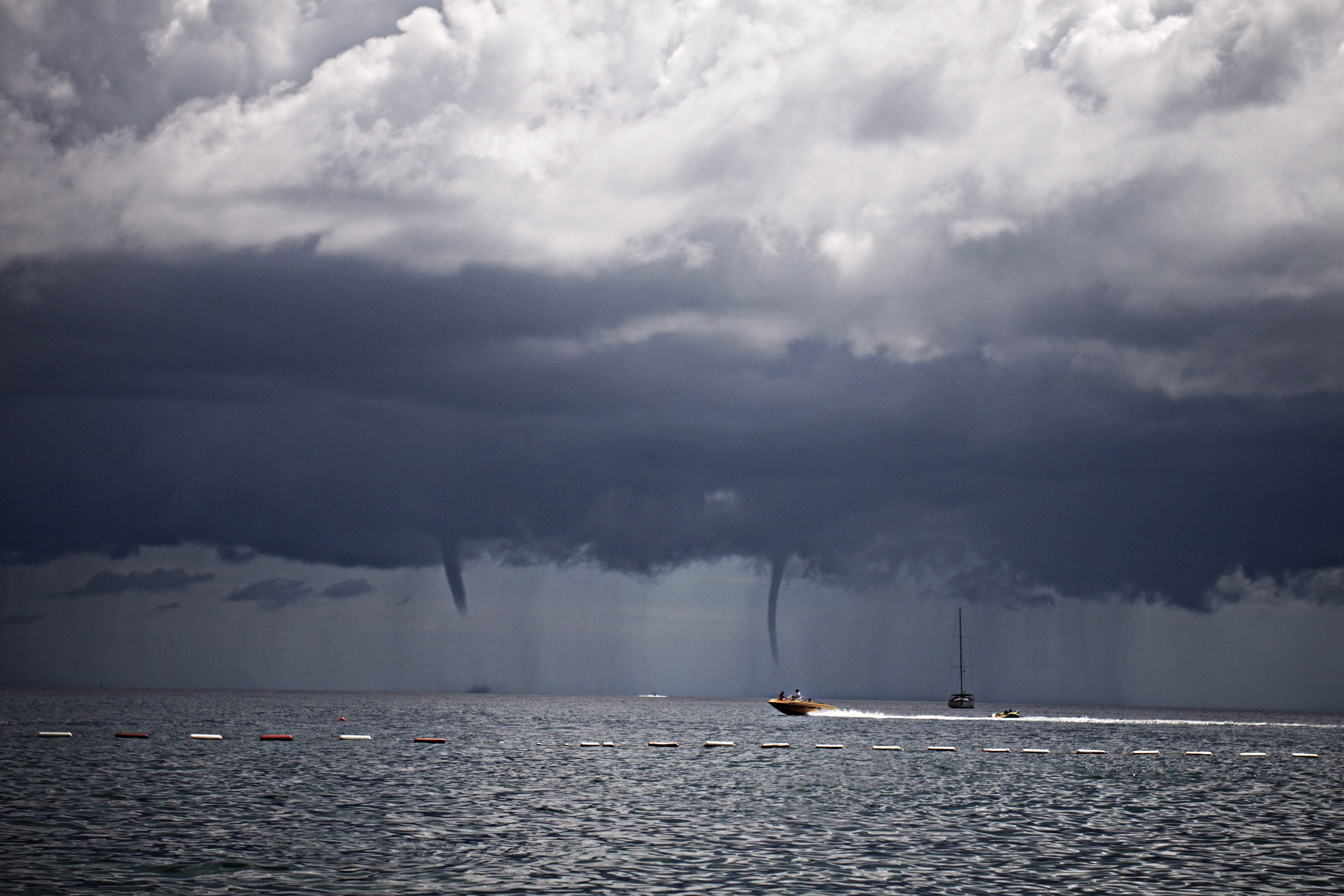Speedboat speeding across the sea with waterspout tornadoes in the distance in Budva Municipality