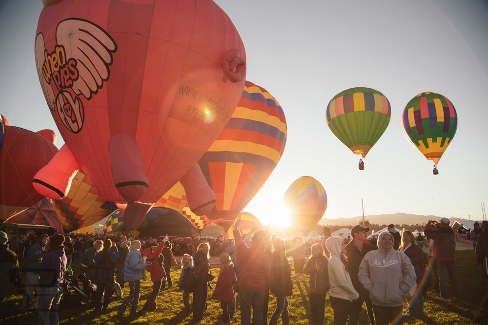 people near assorted-color hot air balloon during sunset