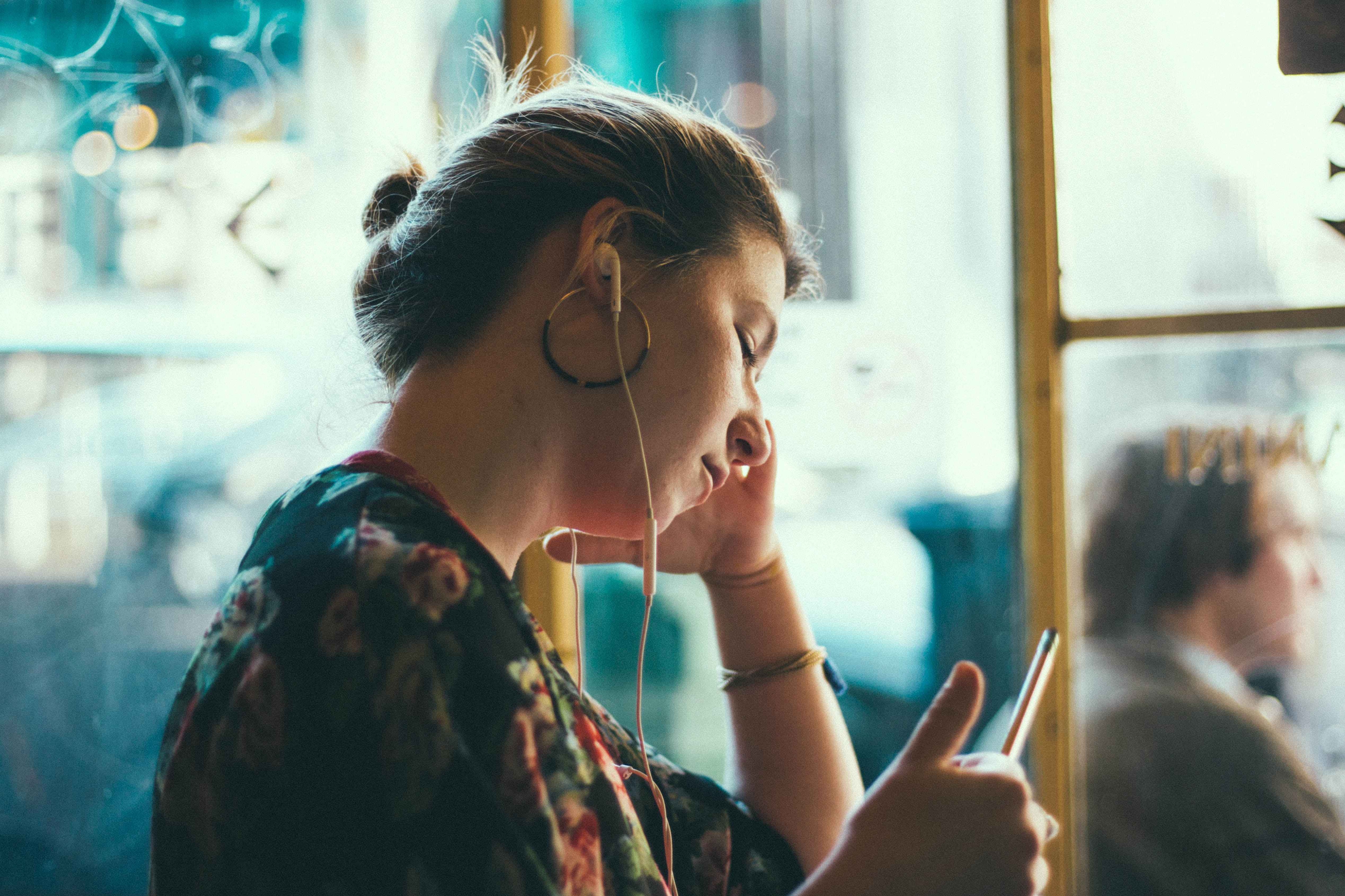 woman listening using white earphones