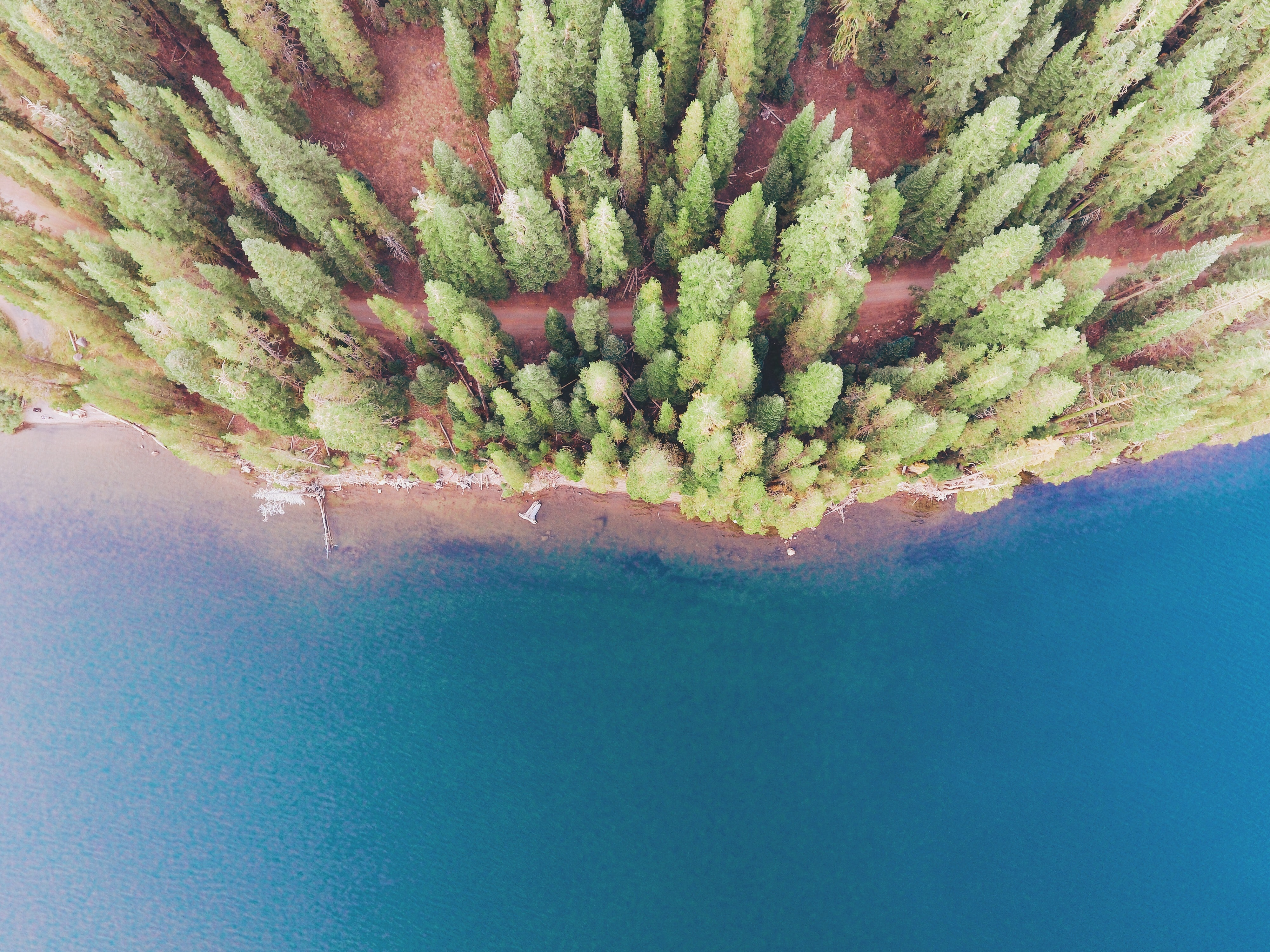 A drone shot of a red dirt path along the shore of a blue lake