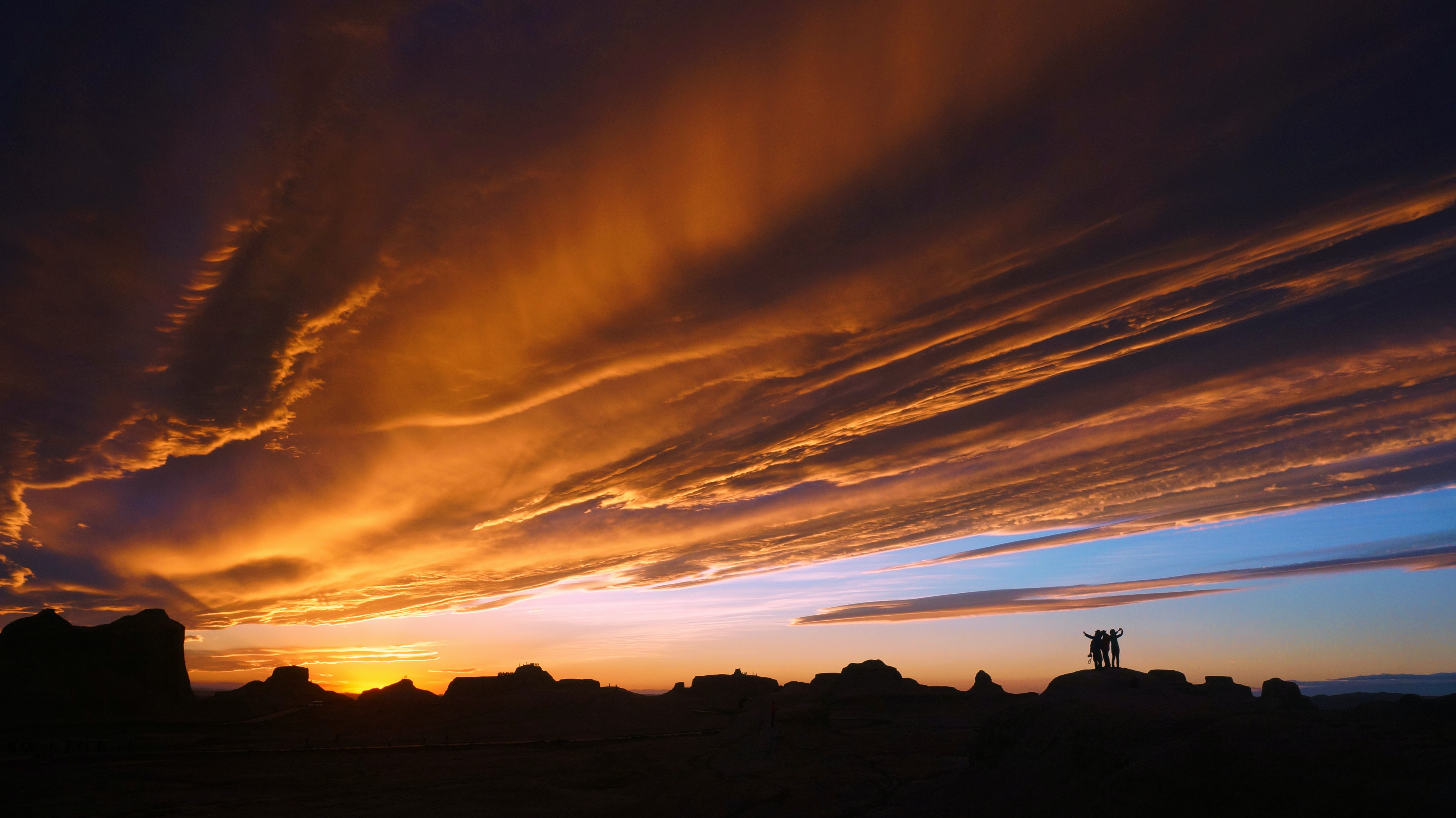 A silhouetted group of friends standing on top of rock formations, with a cloudy sunset overhead in Xinjiang