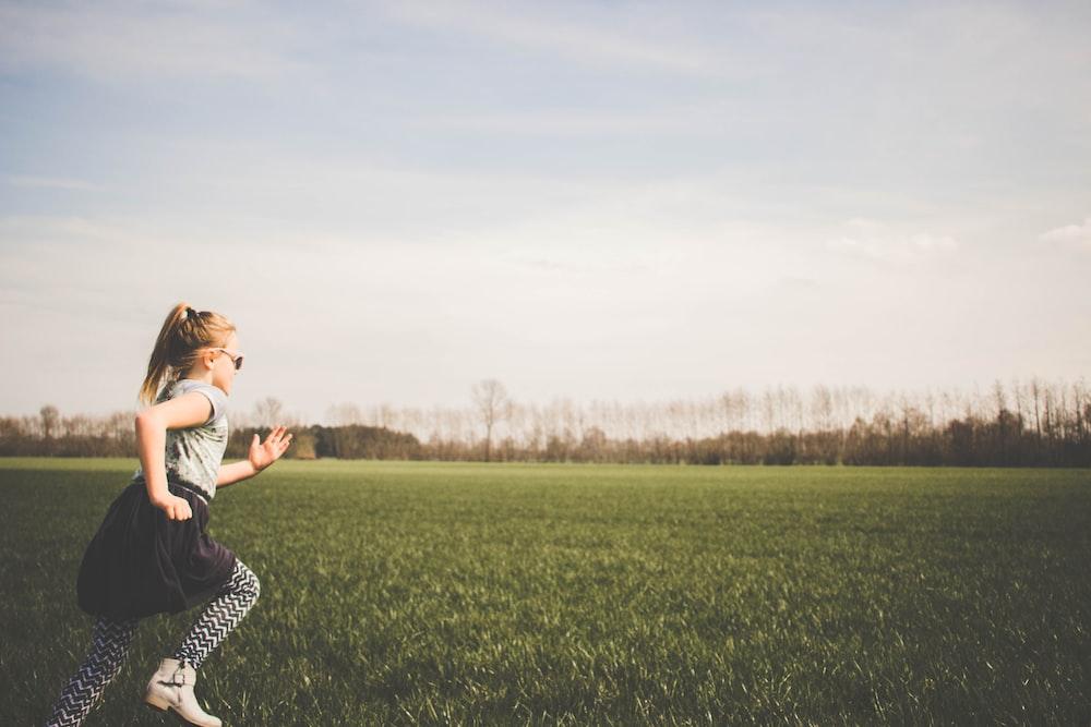 girl running on grass field