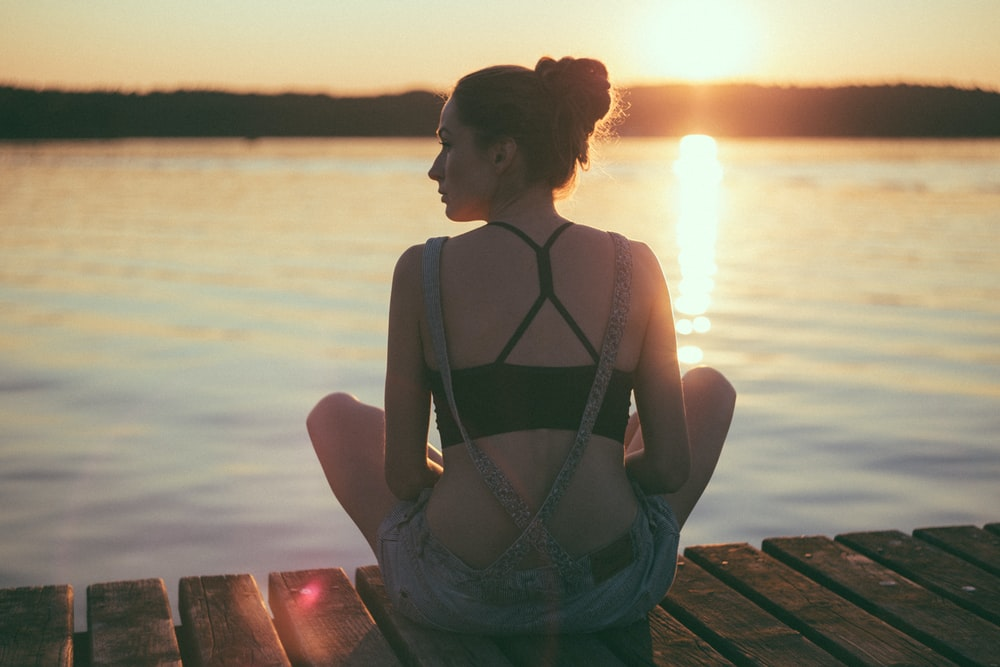 woman sitting on brown wooden dock during sunset