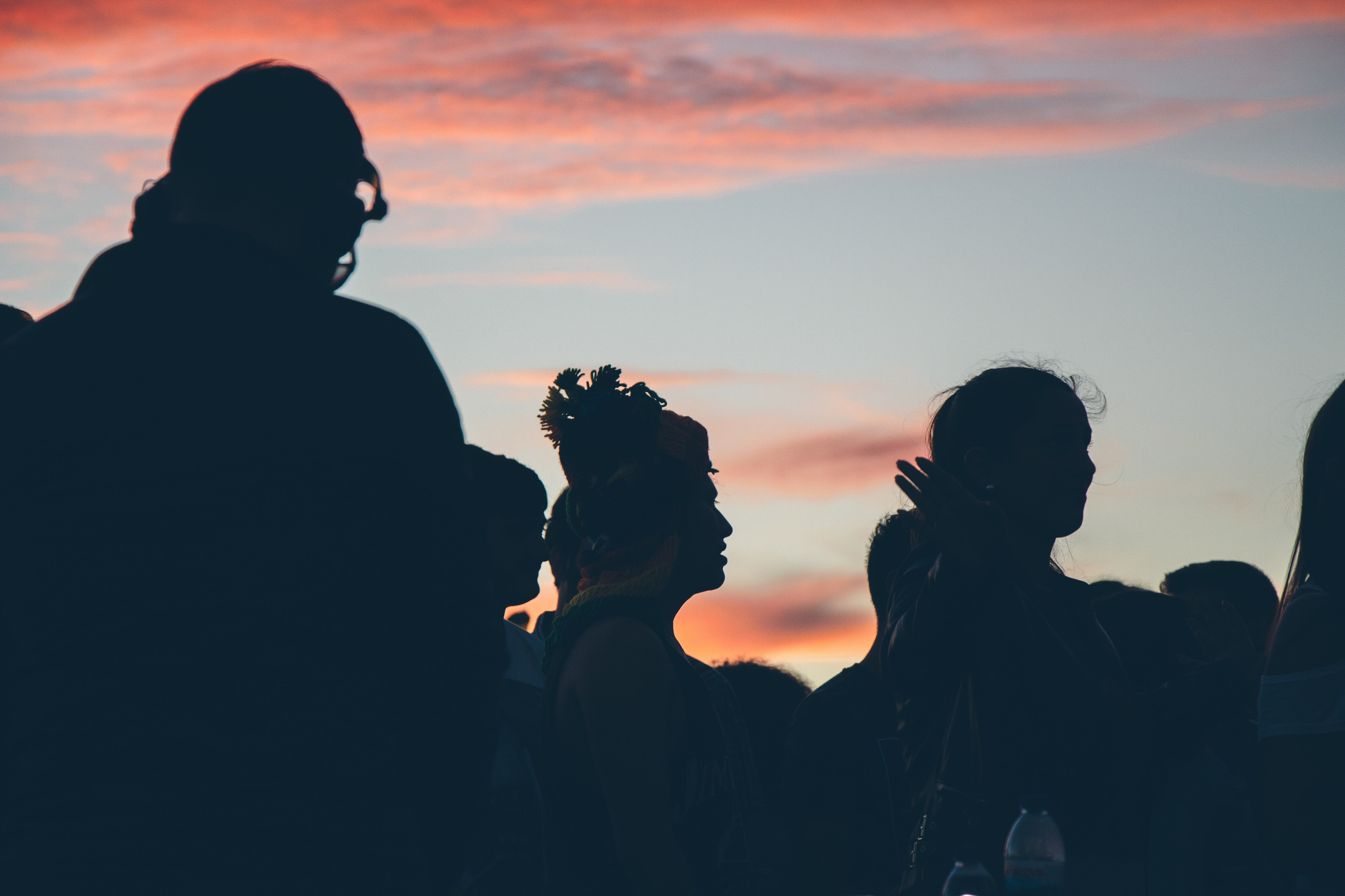 Silhouette of a group of people watching something and standing under the sunset in Leiria