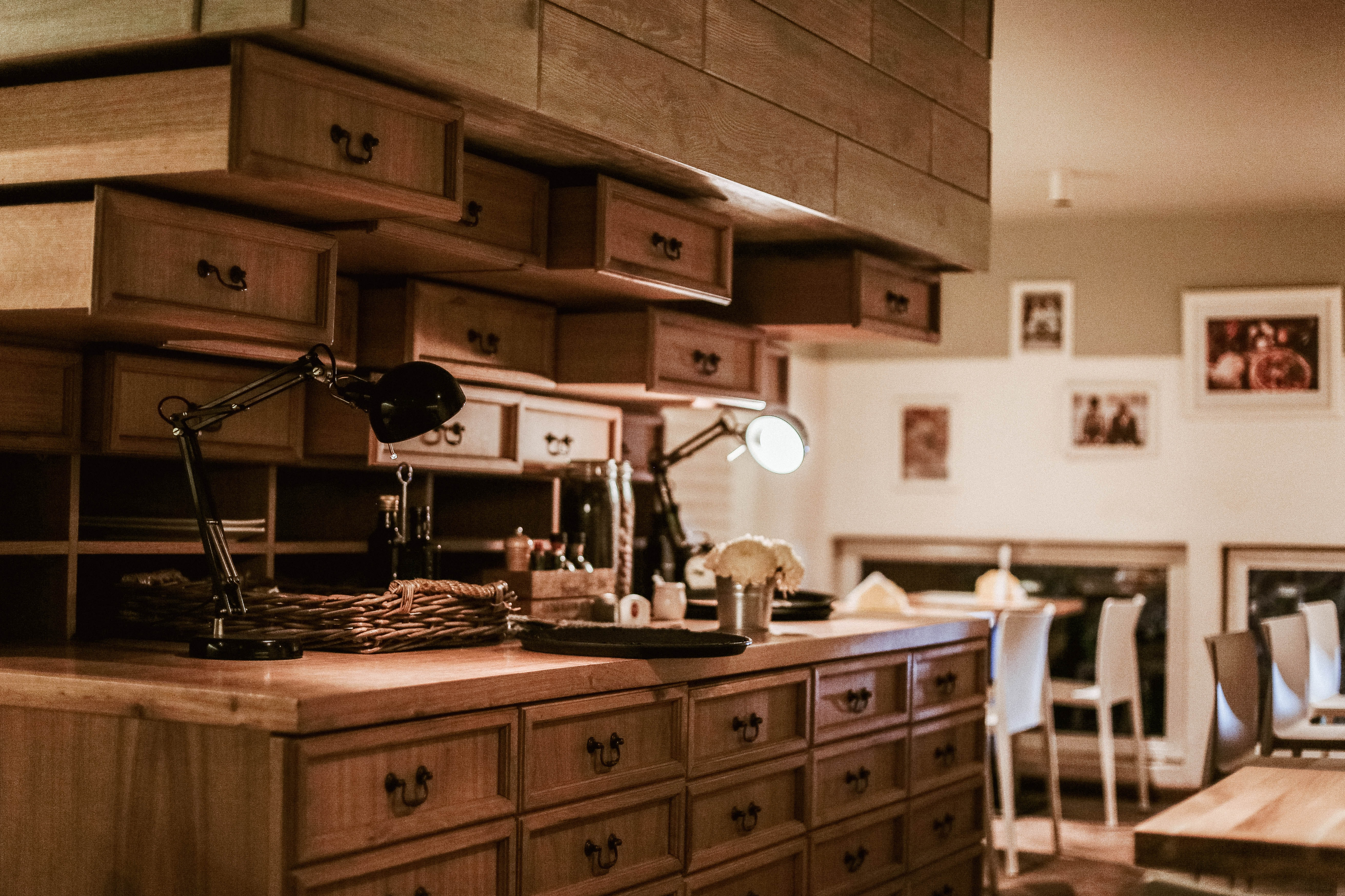 Rows of wooden drawers surrounding a small workplace in middle of well lit room