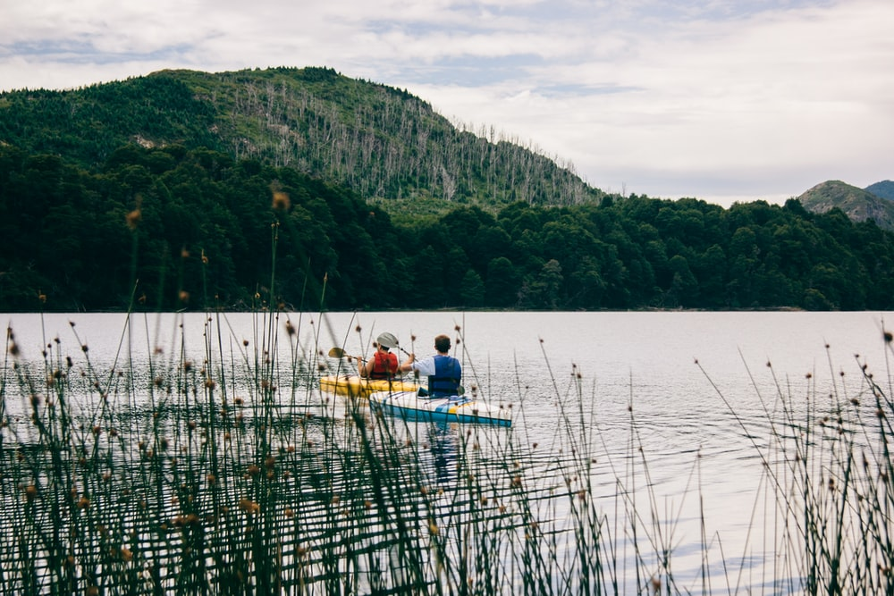 two person kayaking near mountain