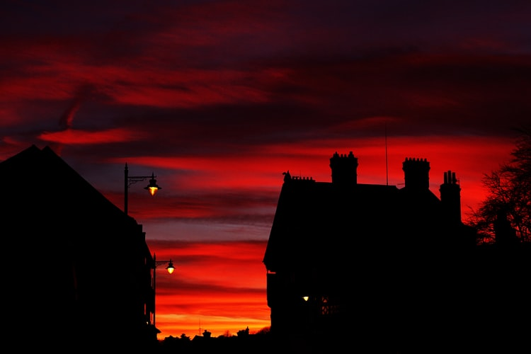 Dramatic red sunset over silhouetted houses