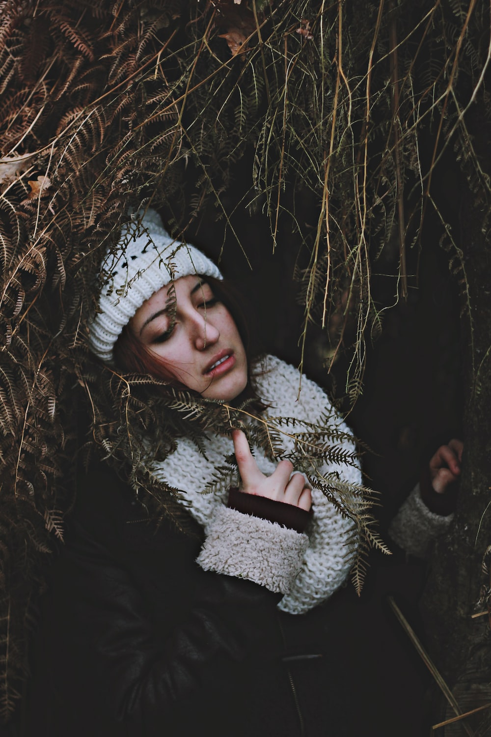 woman under arc of dried leaves holding scarf
