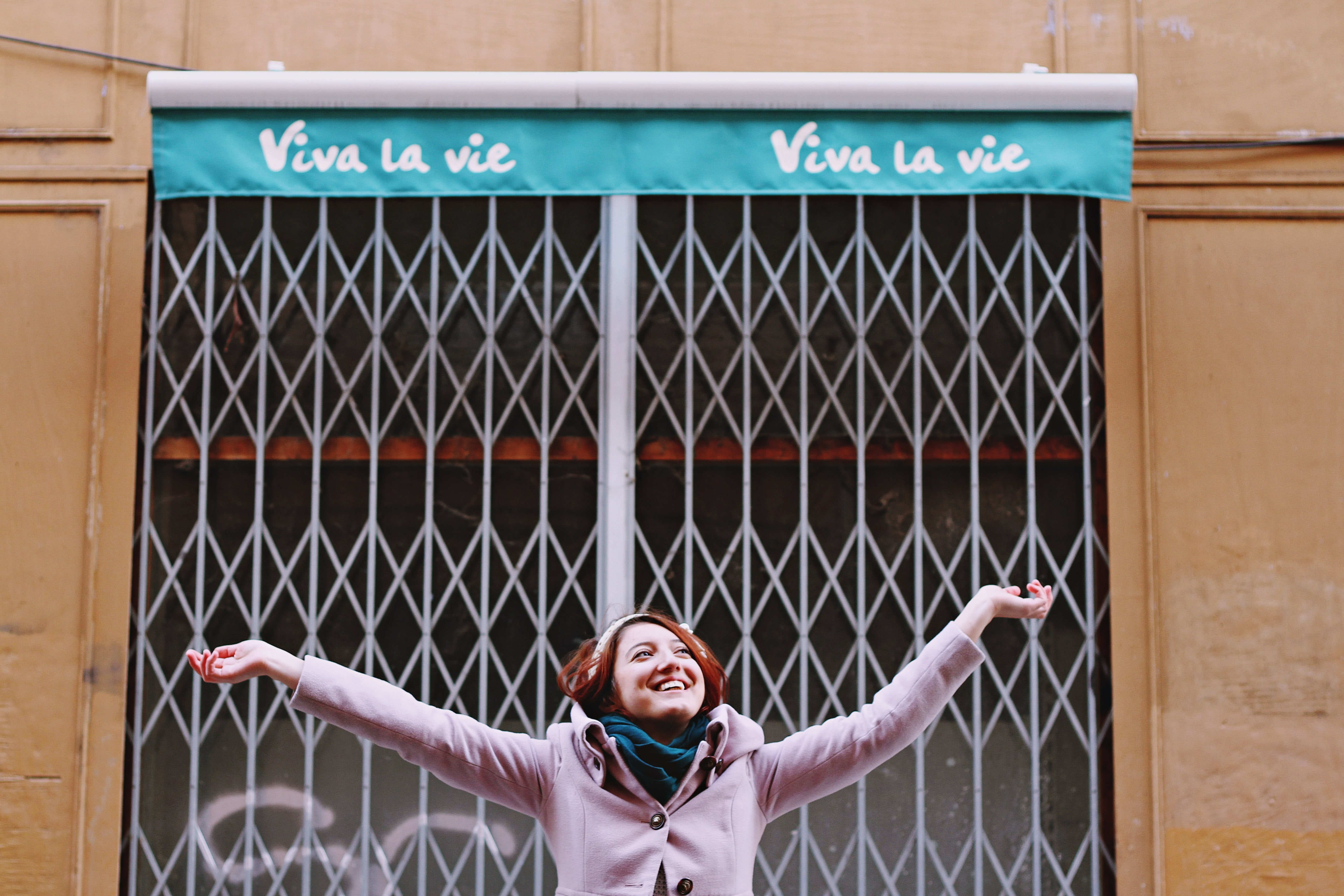 A woman smiling with outstretched arms in front of a closed storefront in Toulouse