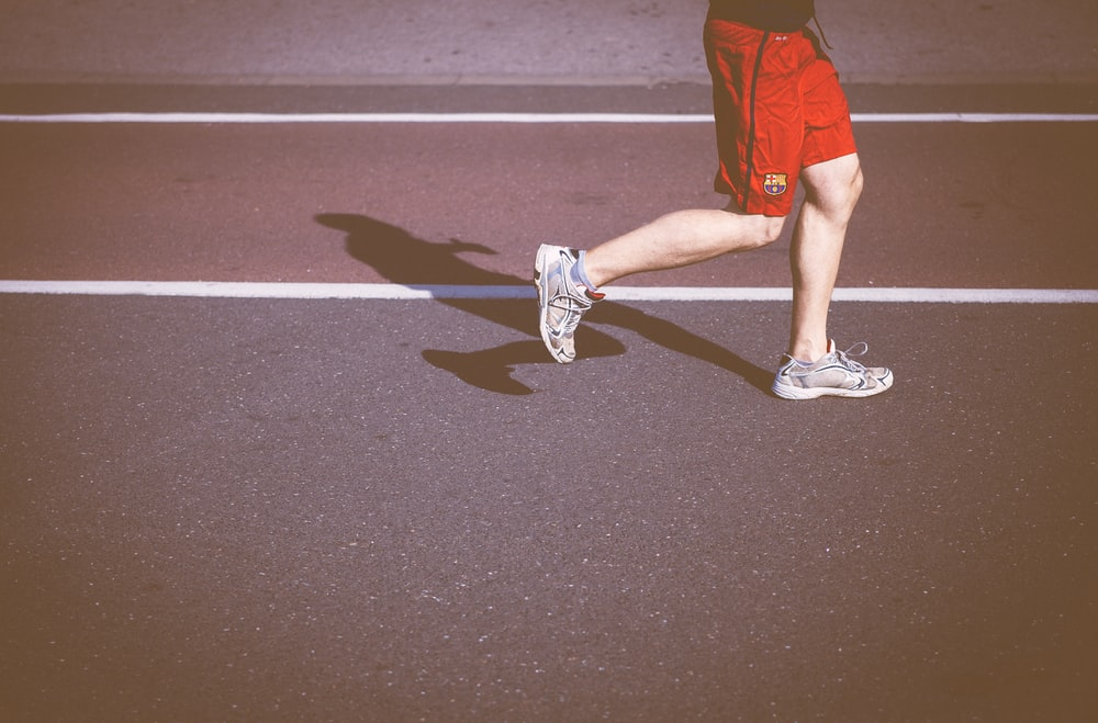 person running on concrete road
