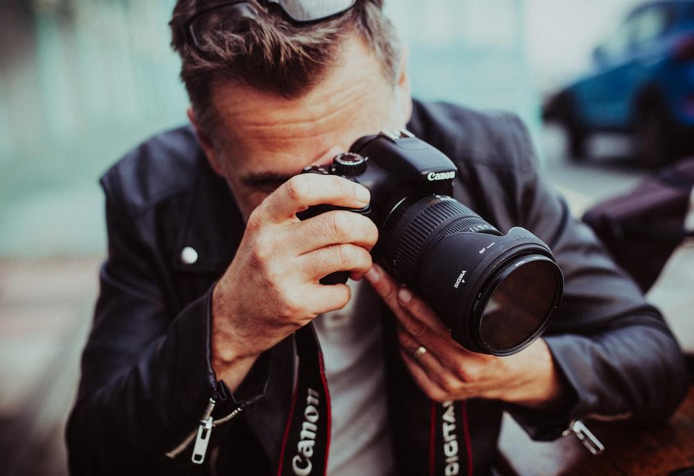 man holding up Canon DSLR camera