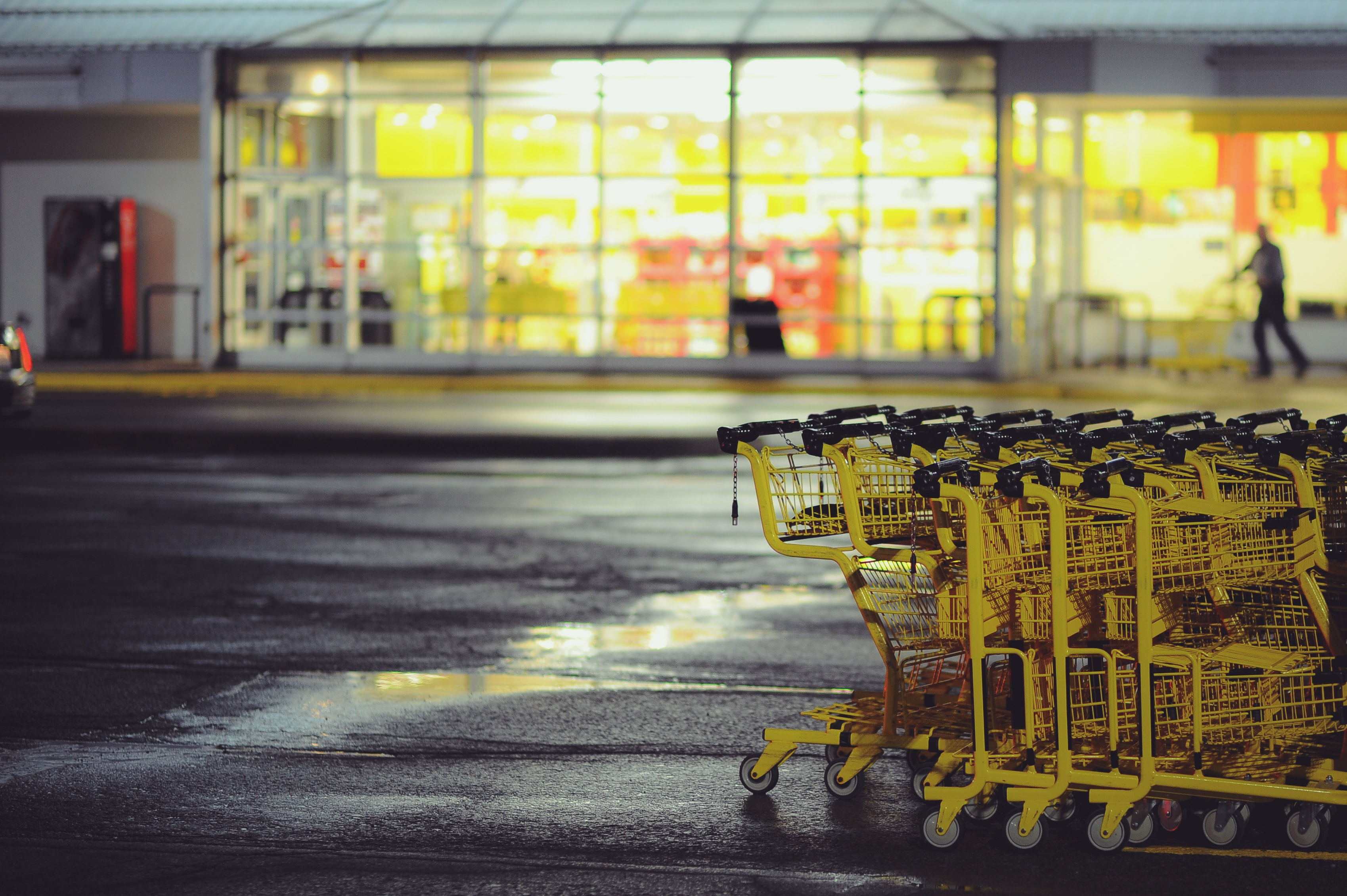 Yellow shopping carts stacked together on the wet parking lot in front of the supermarket at night