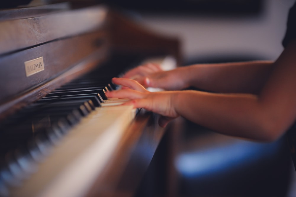 person playing upright piano
