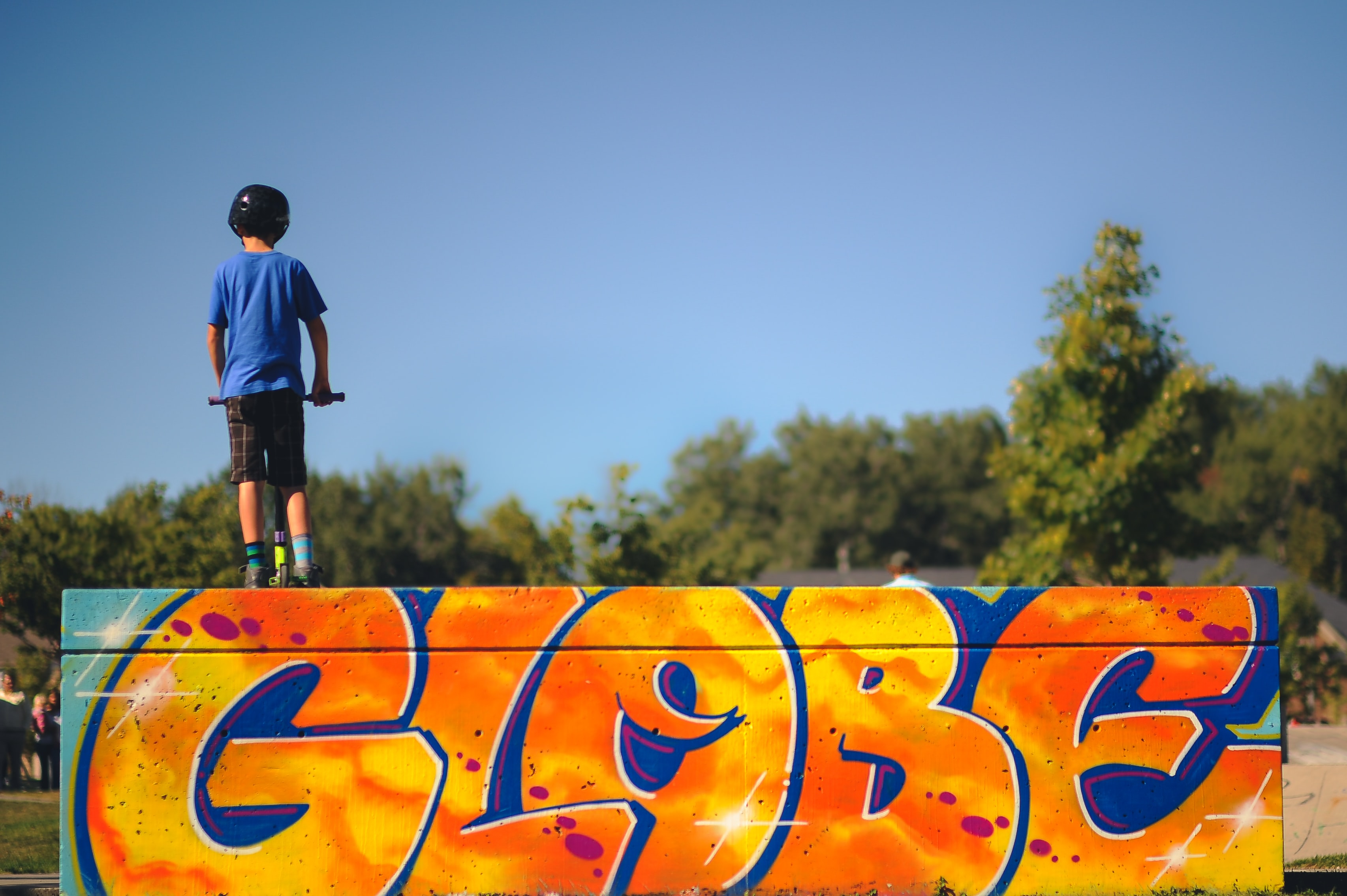 Young child stands atop a graffiti ramp at a skate park