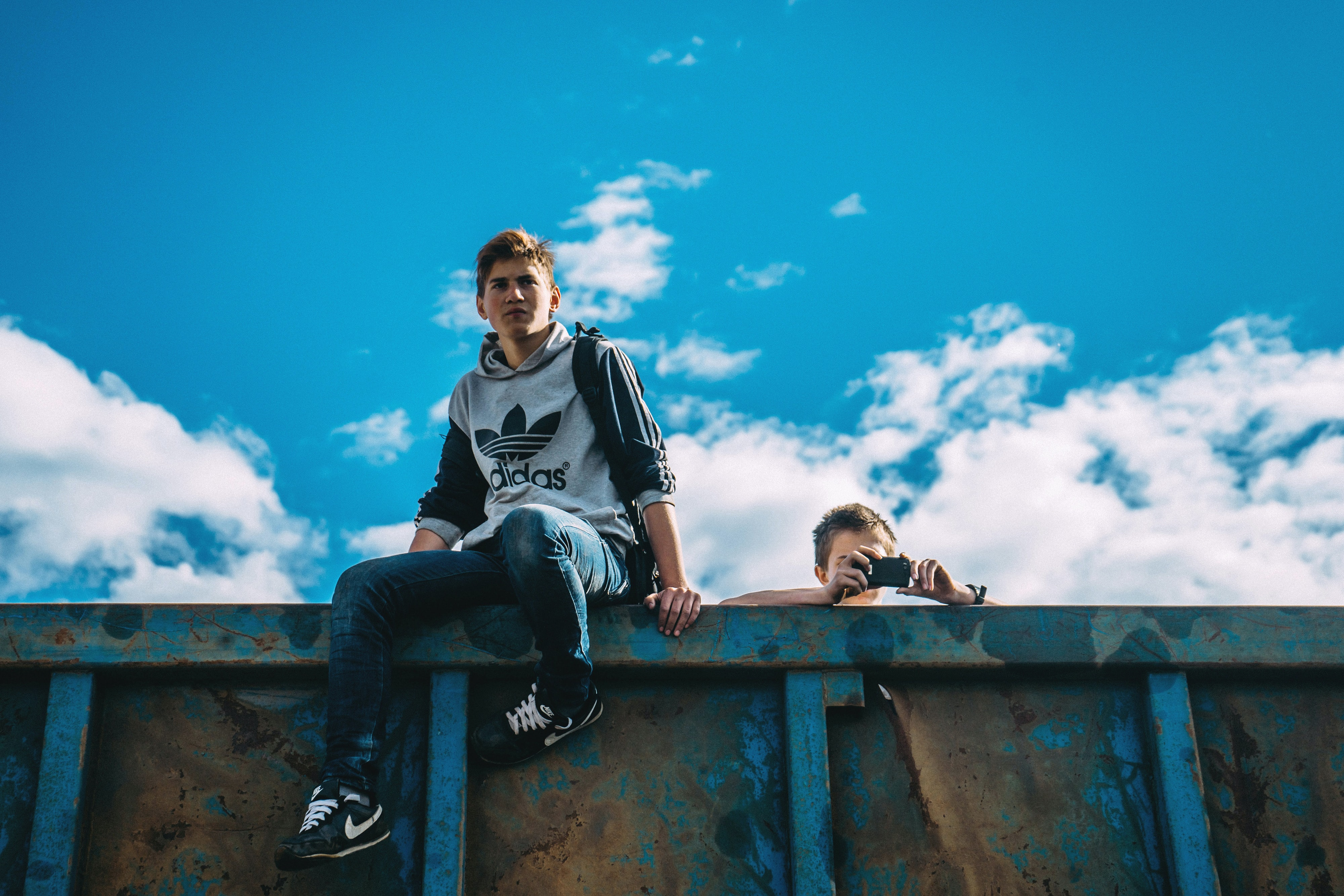 Two men on a rusted wall against a blue sky, one taking photos with an iPhone