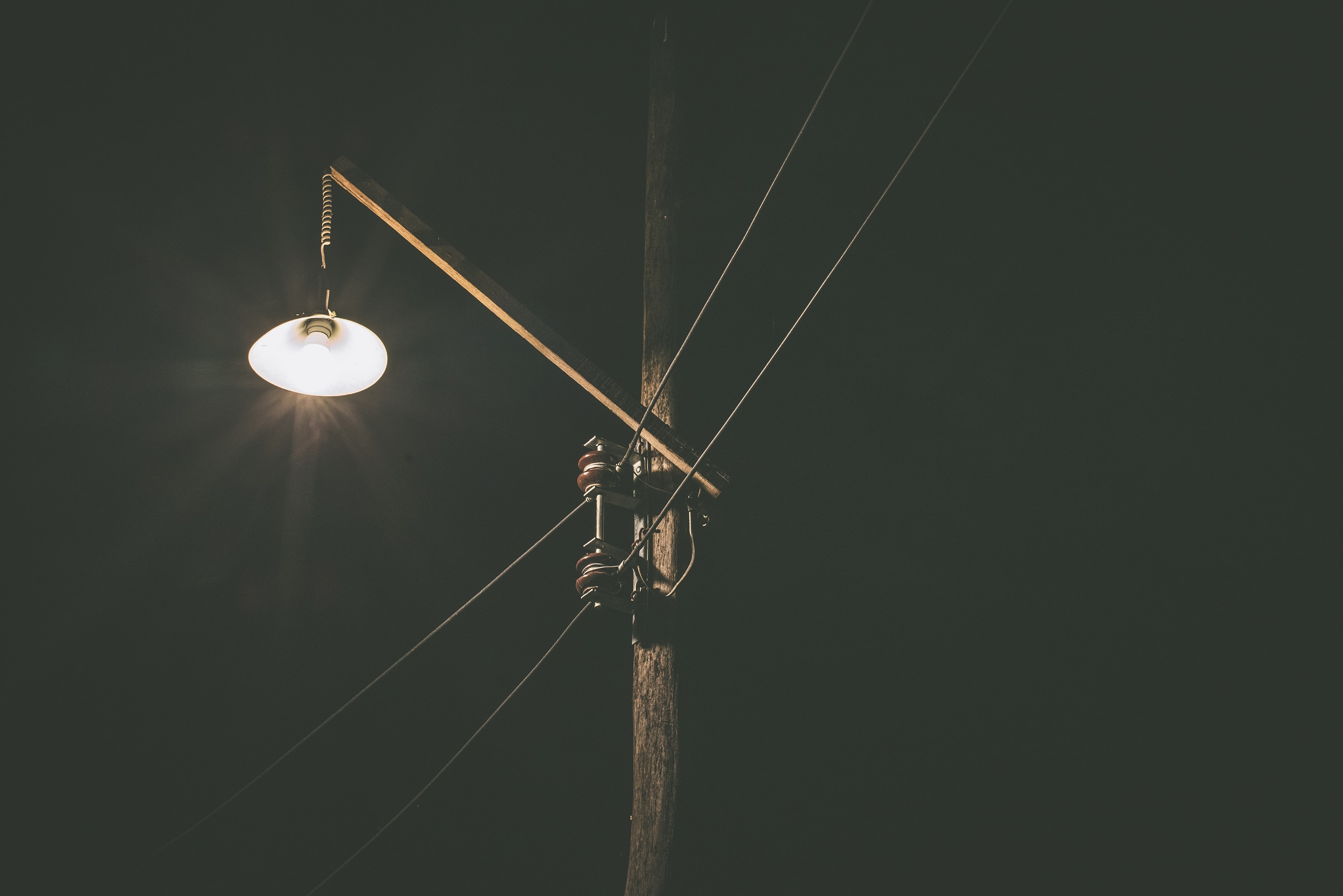Single street lamp lit up by a power line at night