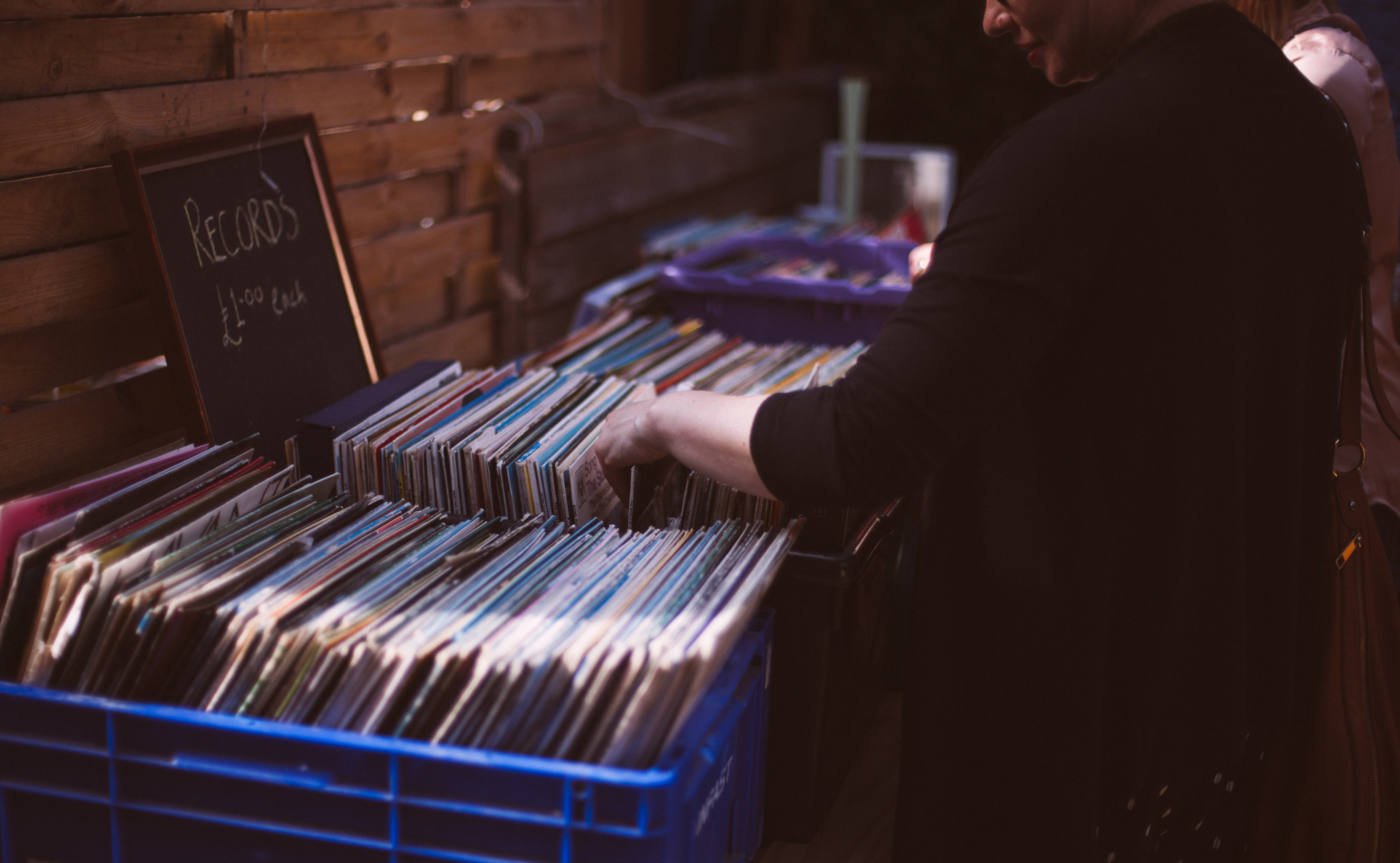 A person browsing a collection of vinyl records for sale in Brighton