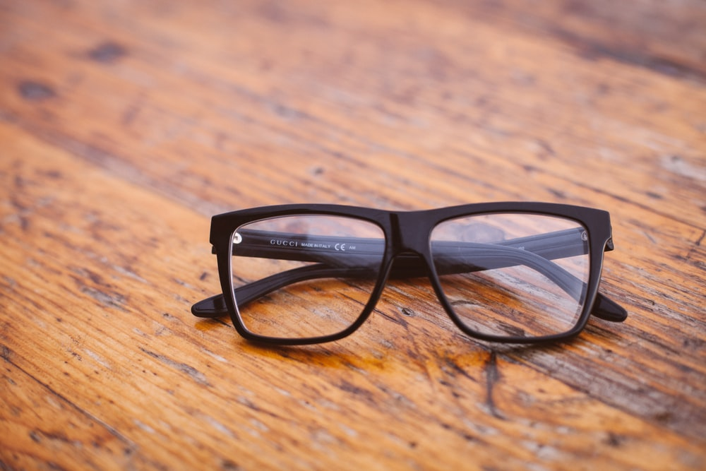 black framed Wayfarer-style eyeglasses on wooden surface