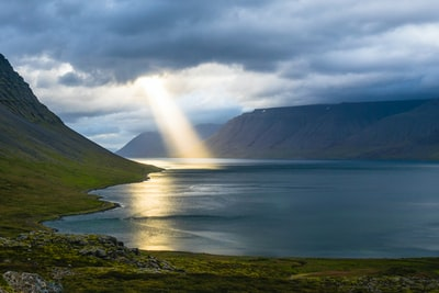 sun reflection on calm water near green mountains