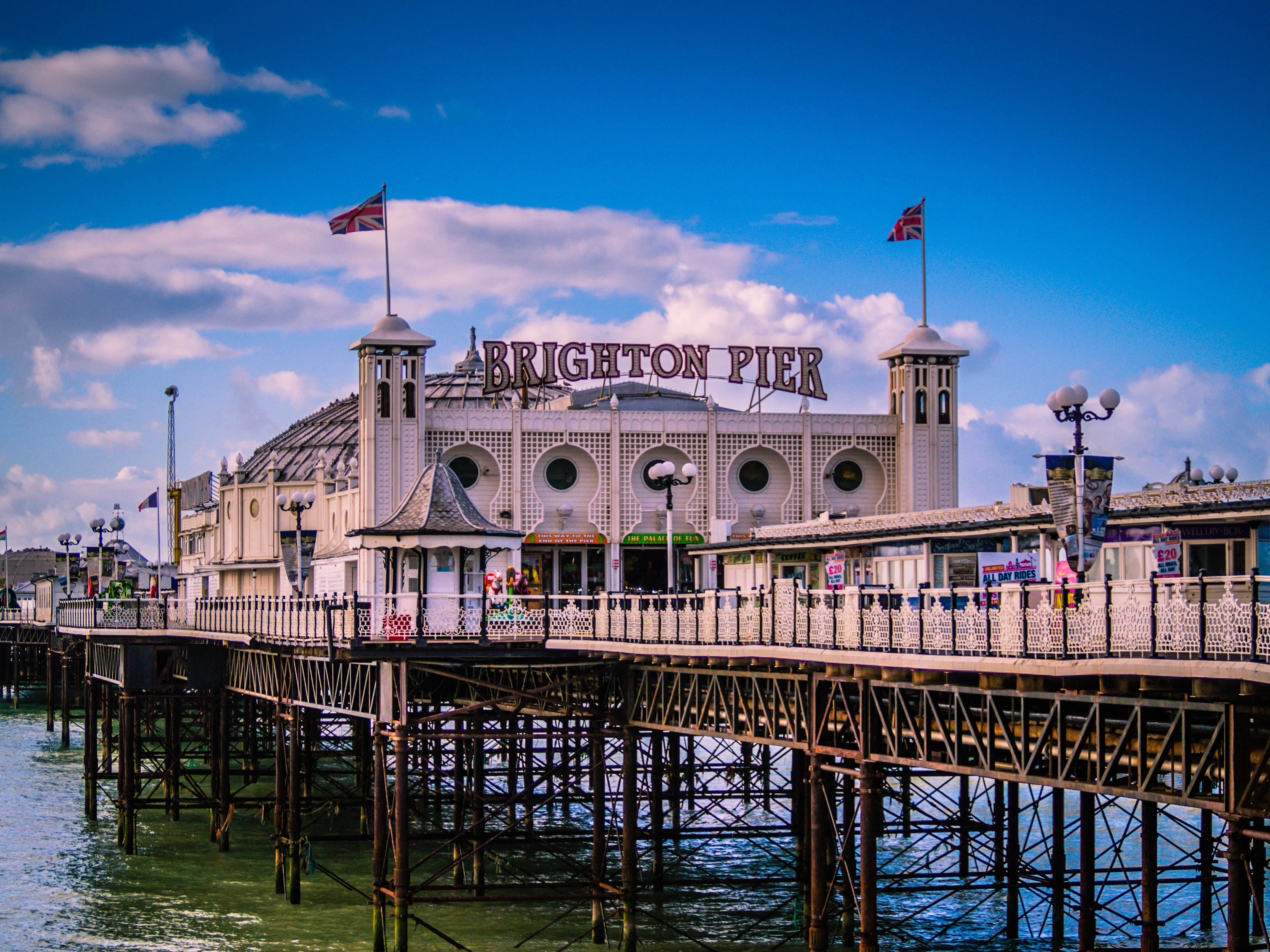 The Brighton Pier on a beautiful sunny day with blue skies and fluffy clouds