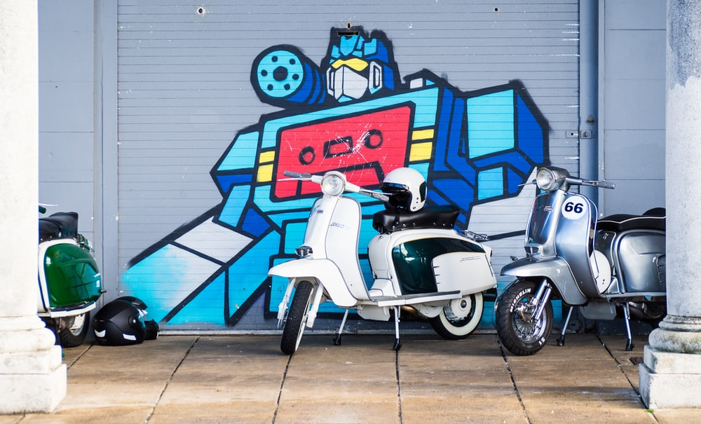 Two White And Blue Motor Scooters Beside Gray Steel Robot Printed Shutter Door
