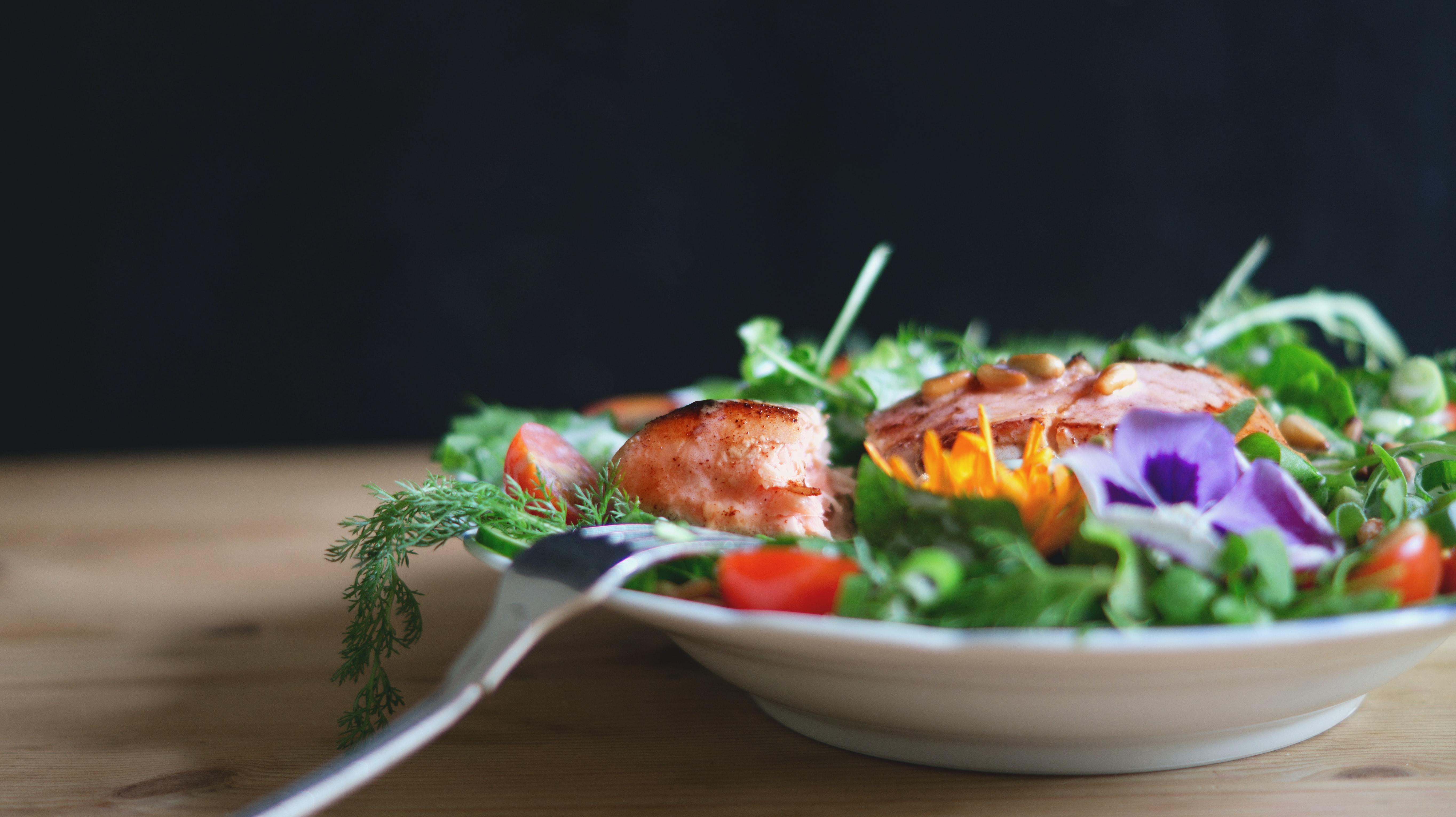 A salad with salmon in a white dish