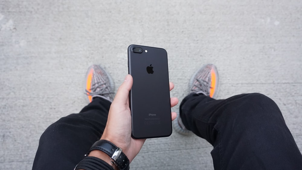 A person holding a black iPhone between their legs.