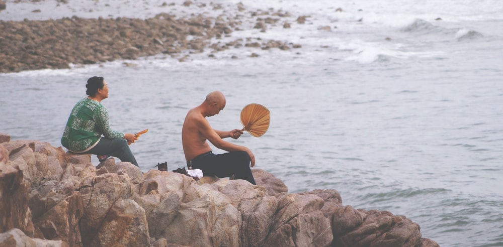 two person sitting on rock facing sea