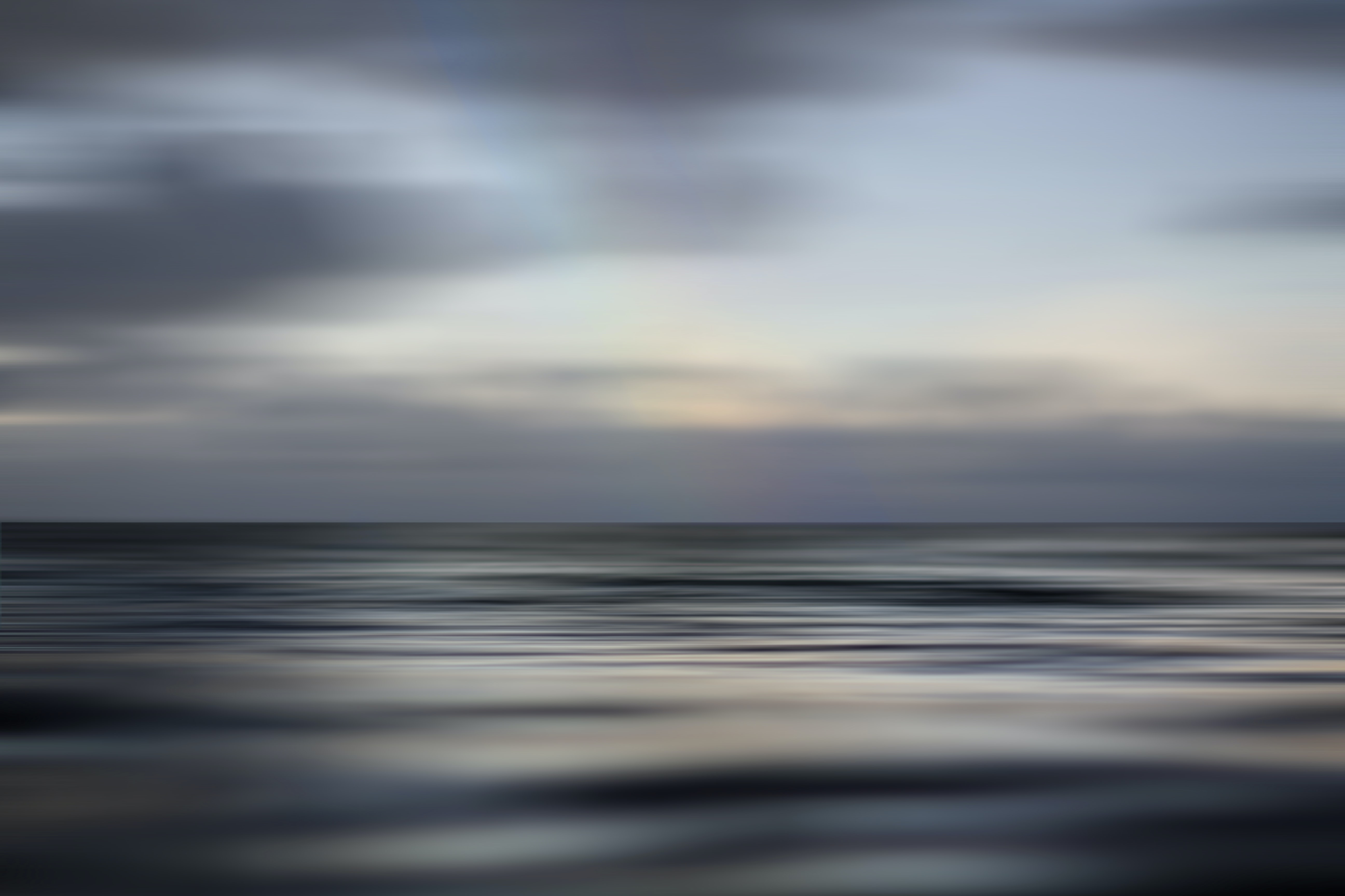 Calm ocean sea horizon shot with cloudy sky and reflection in Spring, Haleiwa