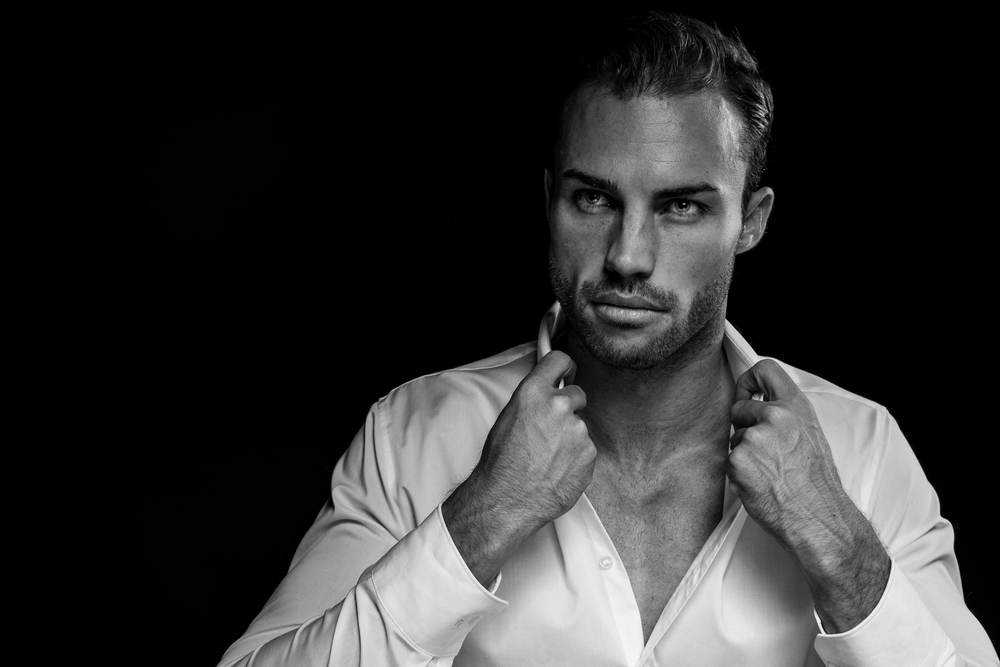 Black and white shot of attractive man on black background posing in white shirt, Frankfurt
