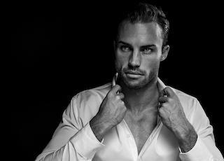 grayscale portrait of man wearing white dress shirt on black background